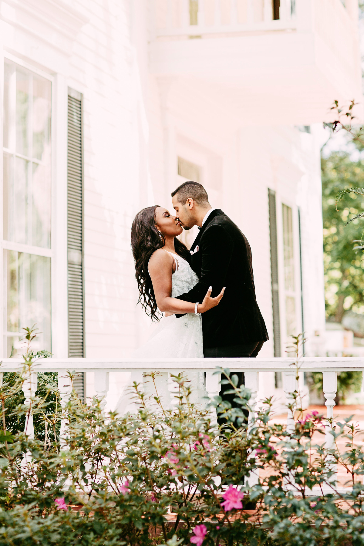 bride and groom kissing on porch