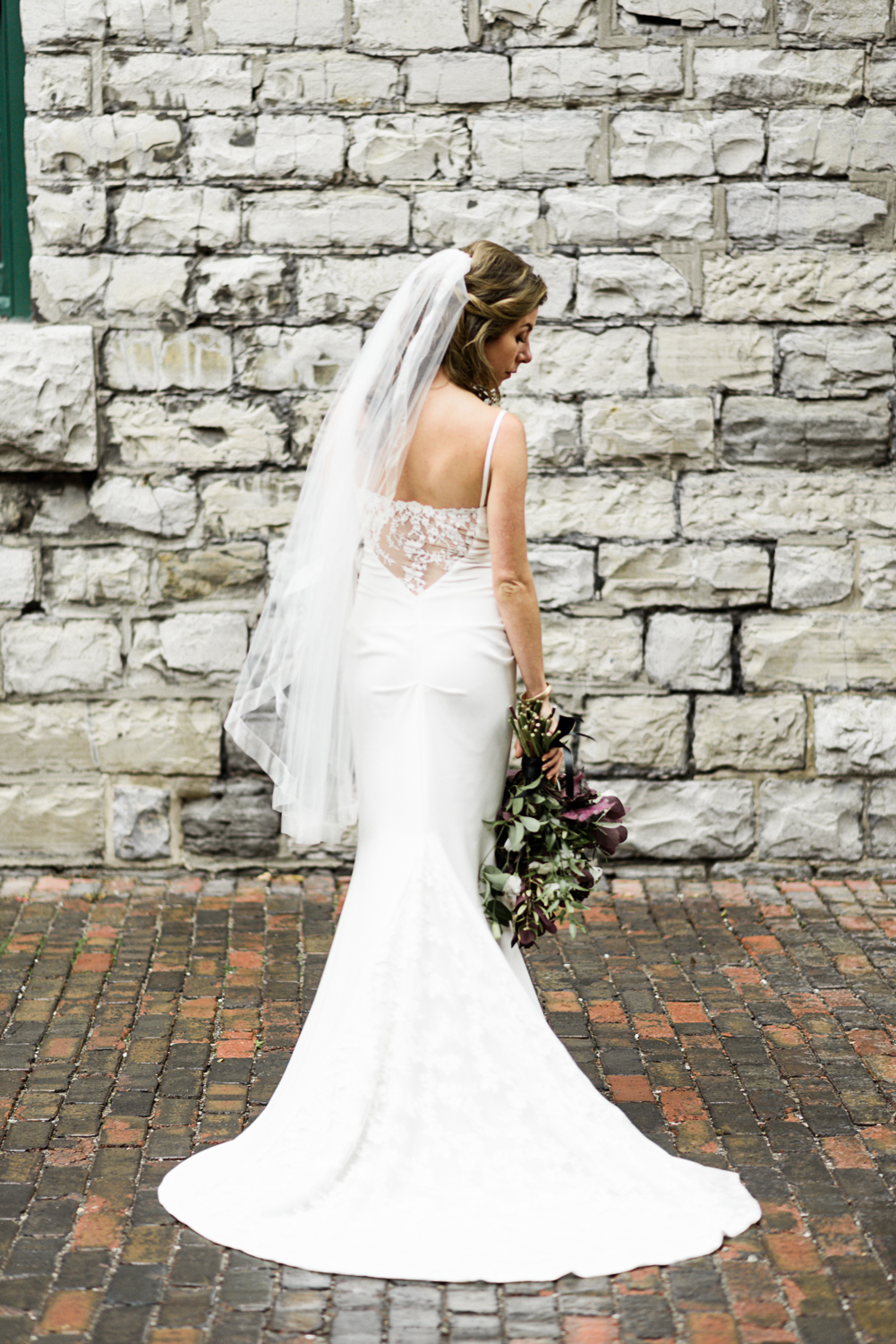 bride stands by stone wall wearing mermaid silhouette wedding gown