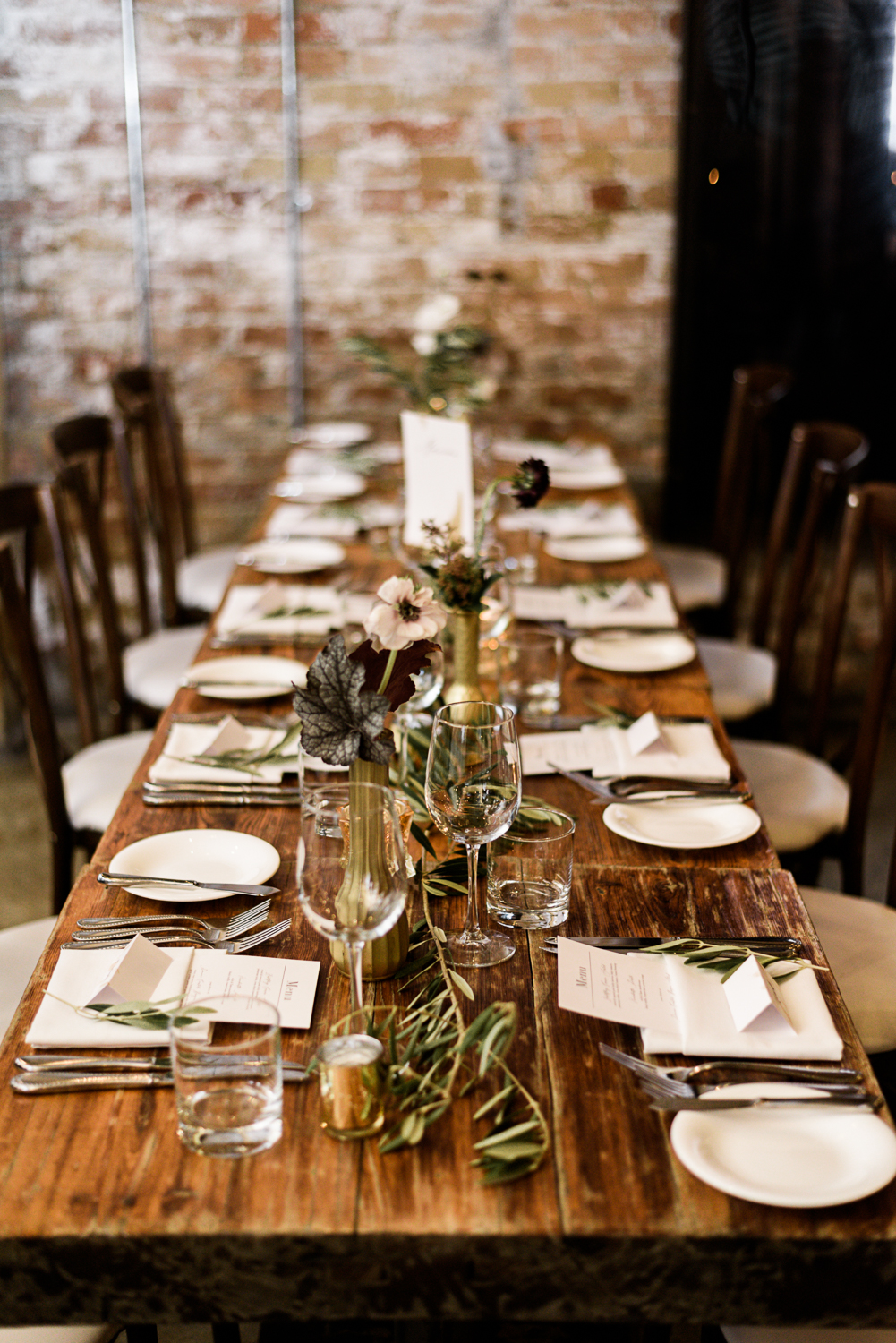 olive branch, white rose, and burgundy floral table displays