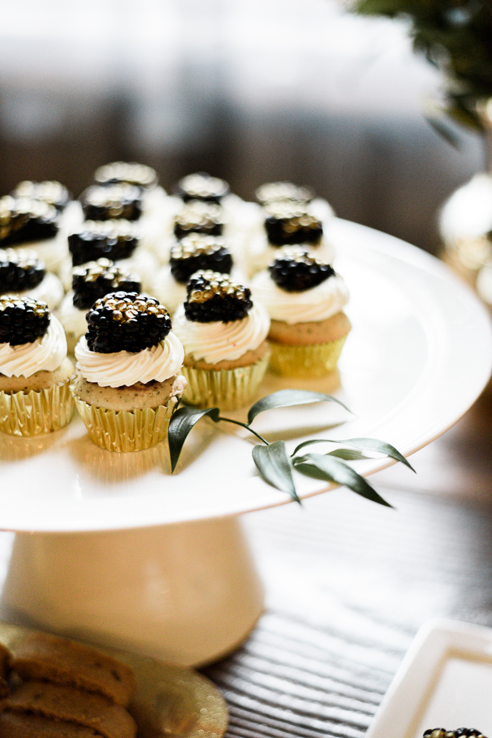 mini cupcakes in gold wrapping on white serving platform