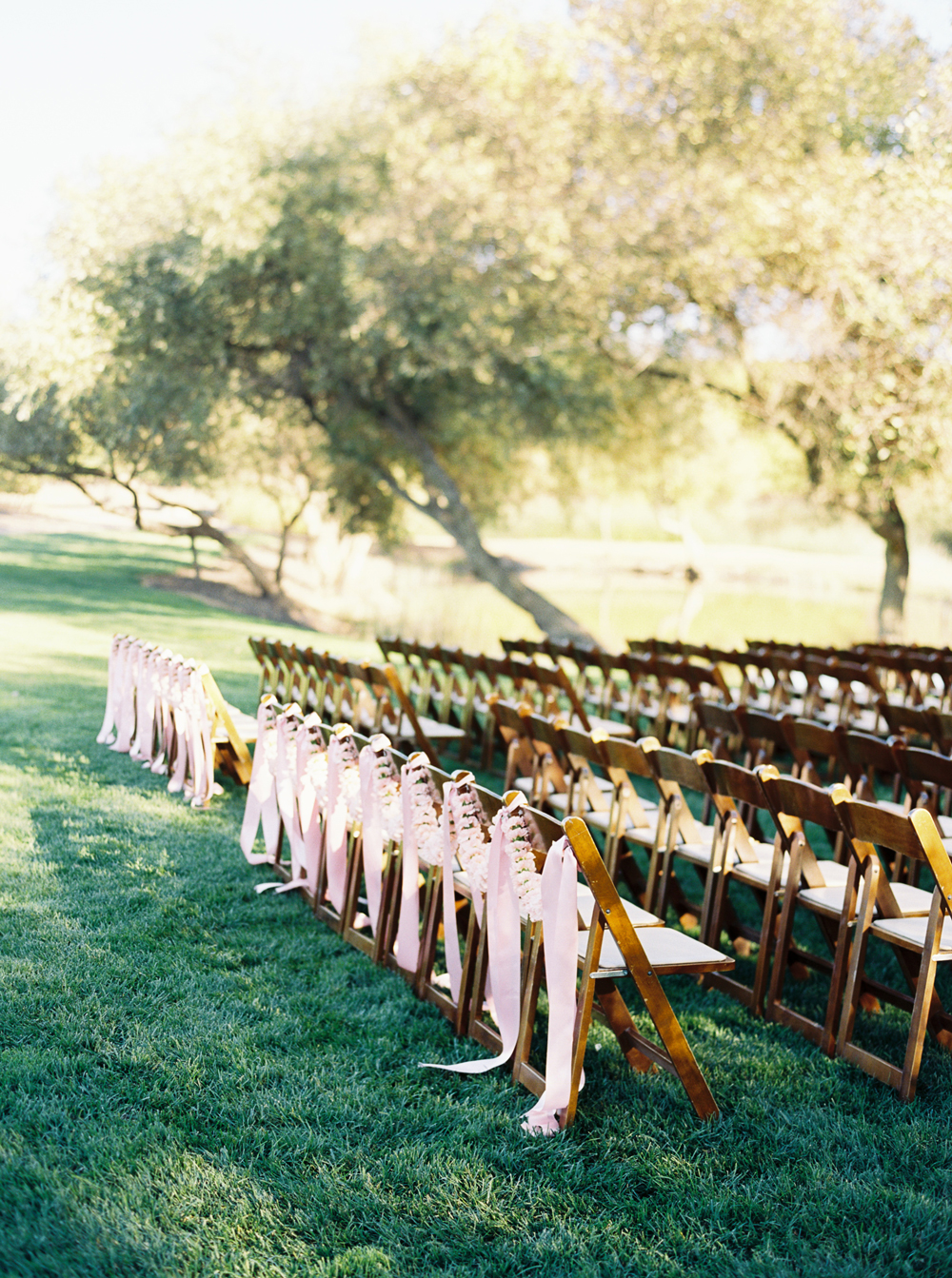 last row ceremony chair decorations pink flowers and ribbon