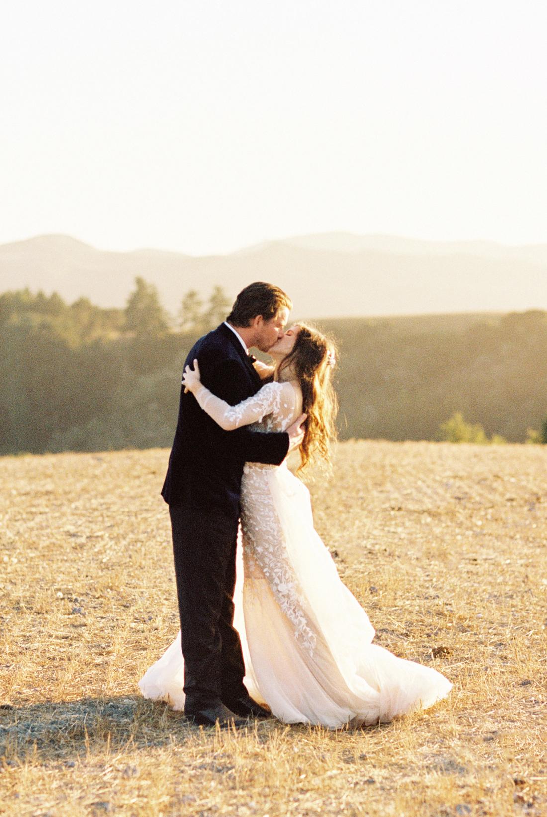 bride and groom kissing on california hillside