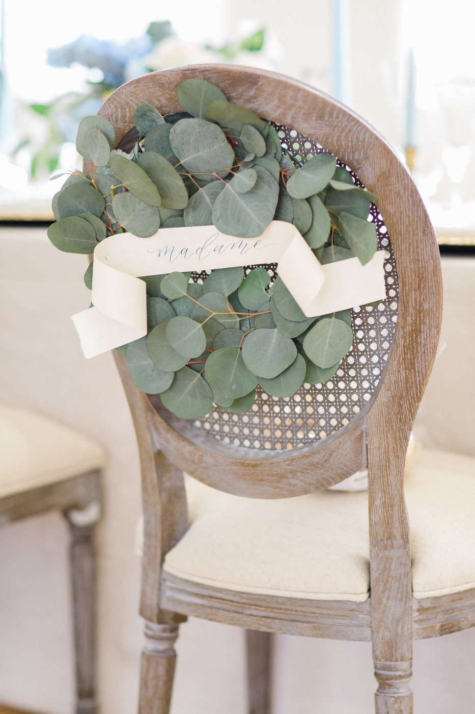 reception chairs with eucalyptus arrangements and paper scrolls