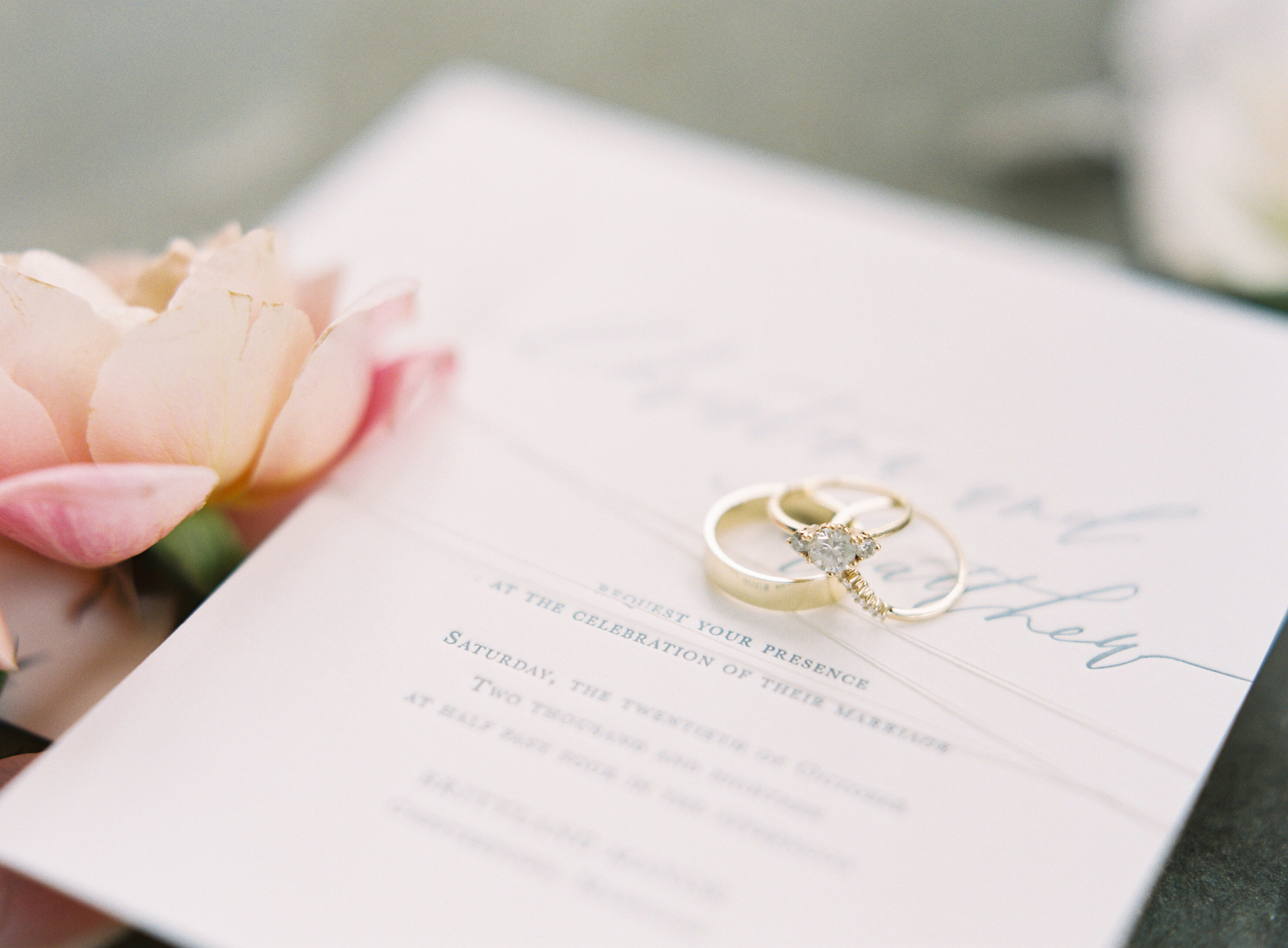 wedding bands diamond ring over invitation