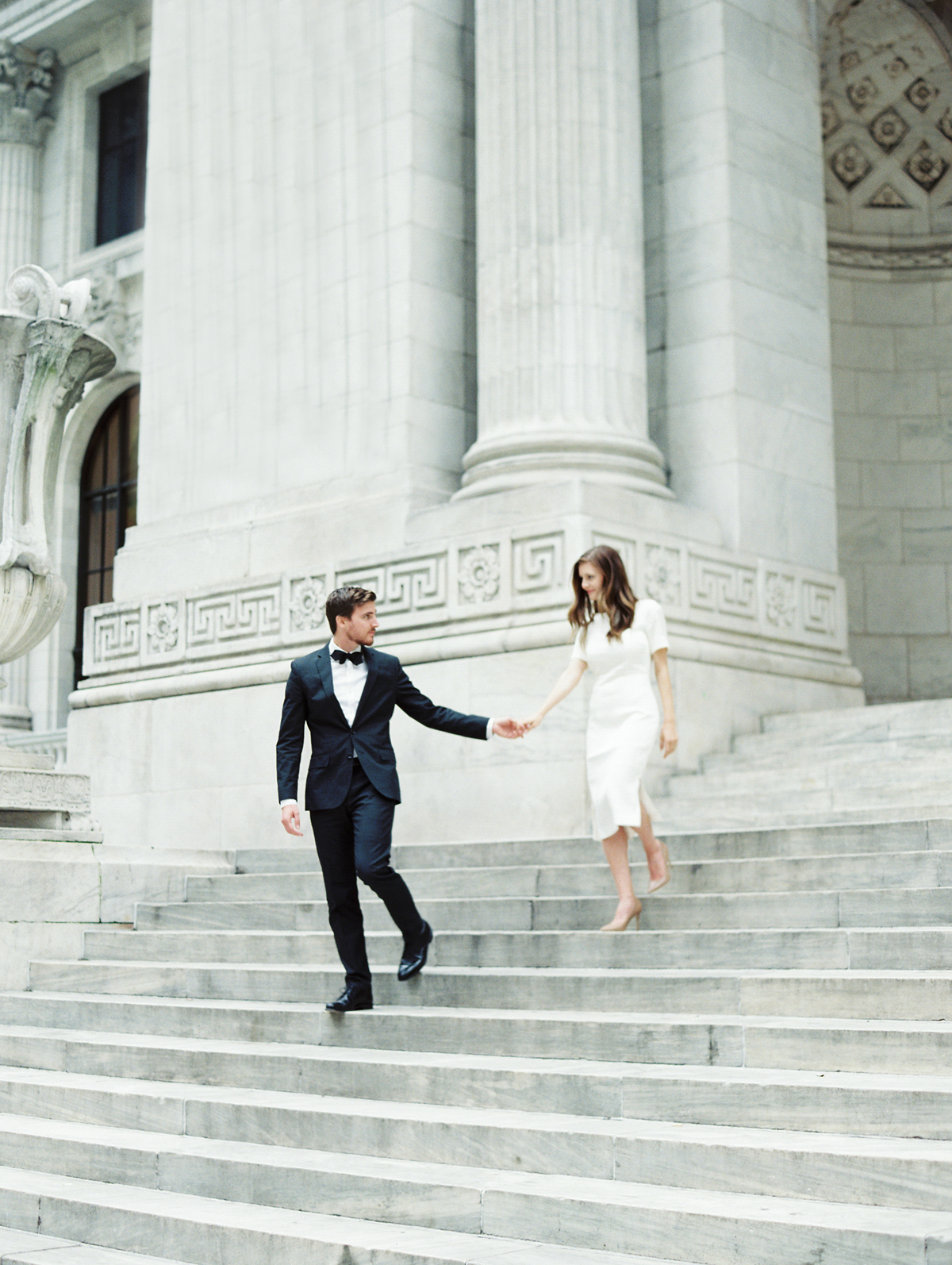 city hall wedding groom holding brides hand descending stairs