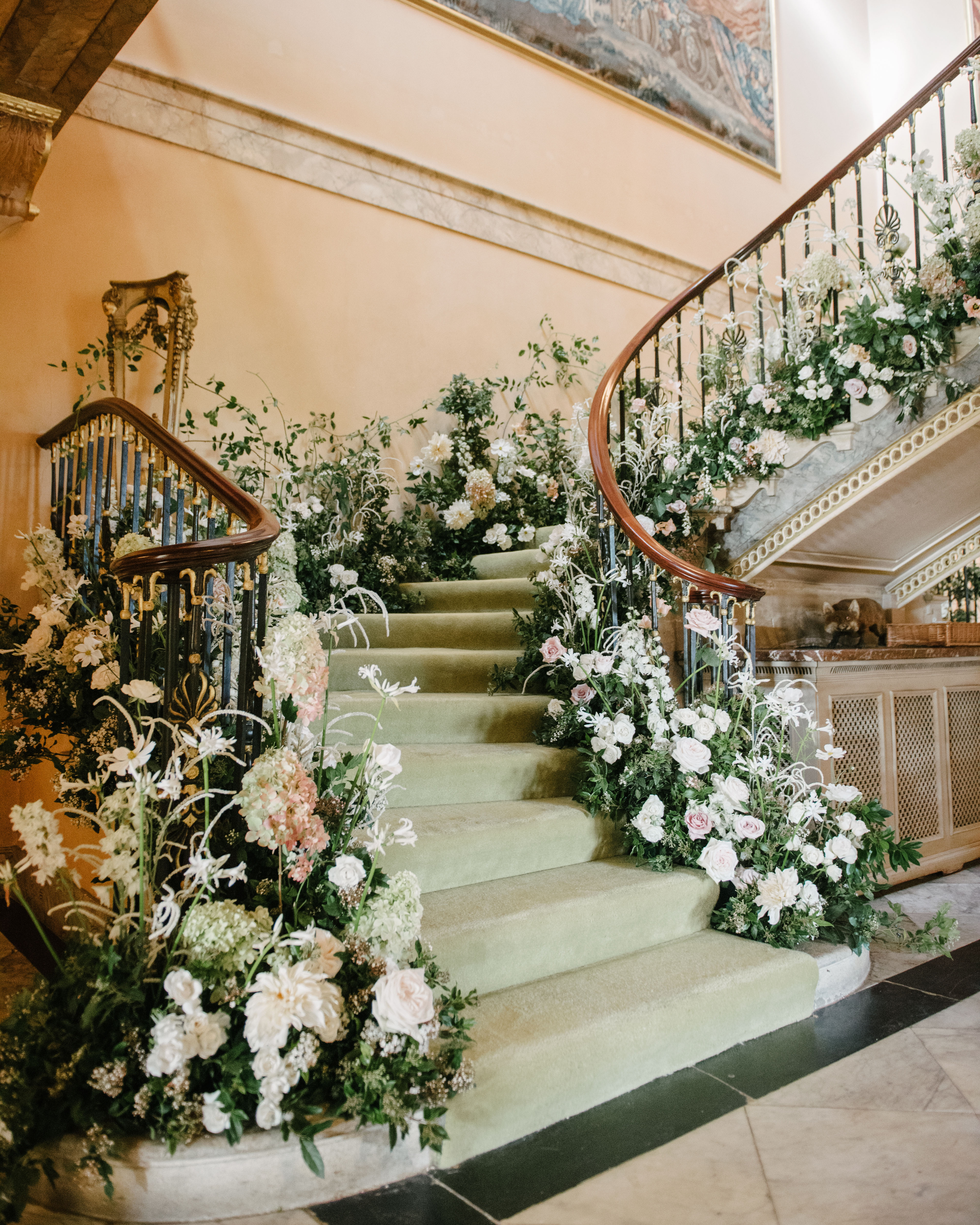 winding stairs banister flowers and greenery decor