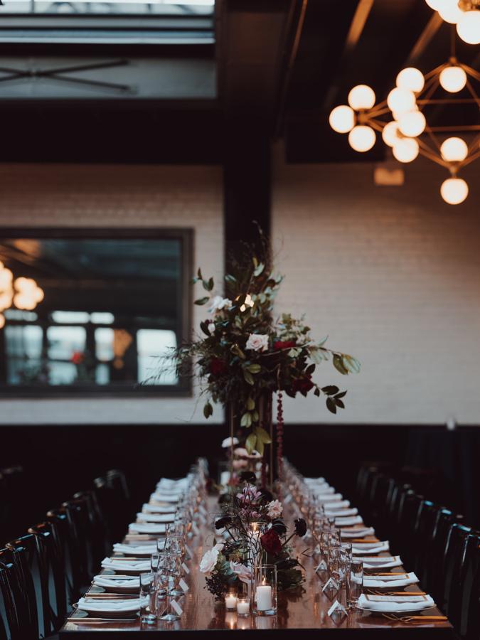 long reception table multiple floral arrangements