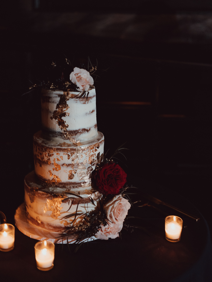 three-tier semi-naked wedding cake with floral decor and gold foil accents