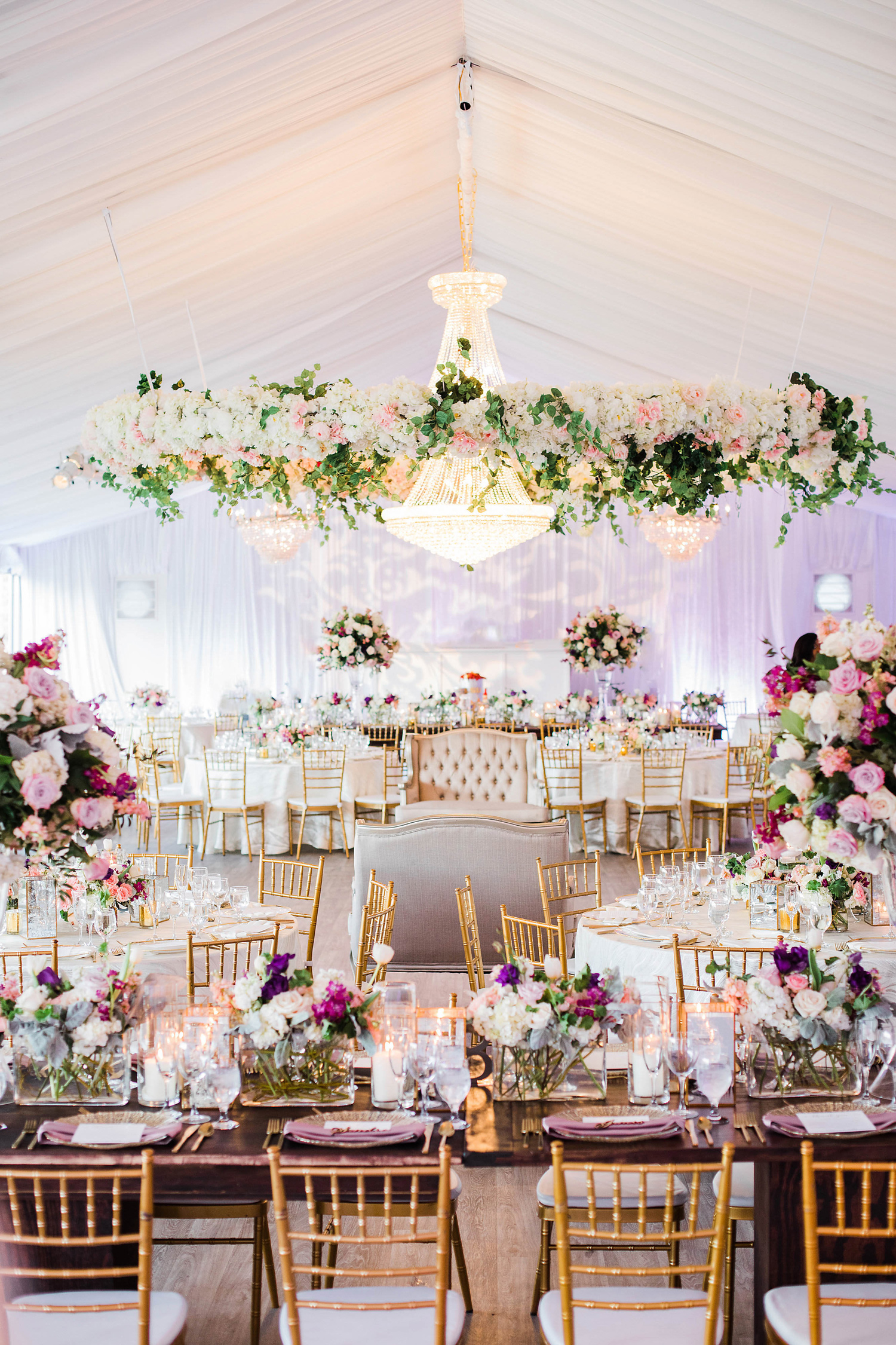 white tent wedding reception filled with hanging floral displays, centerpiece arrangements, and white and dinning furniture