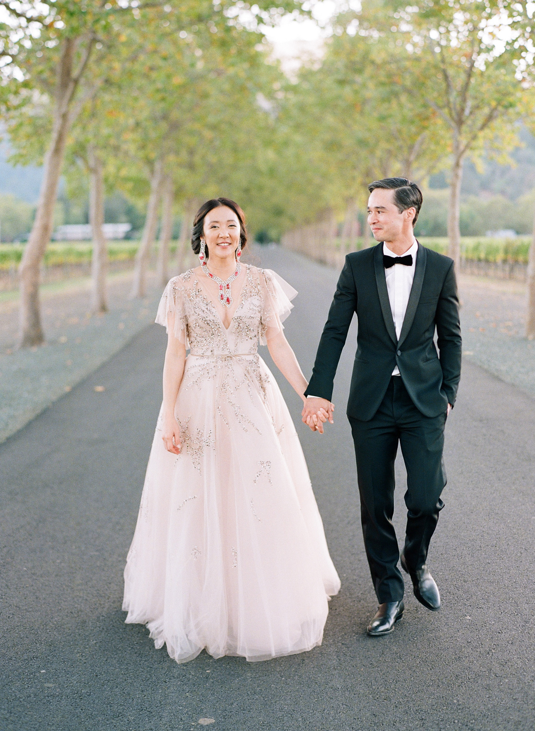bride and groom hold hands smiling on paved walkway