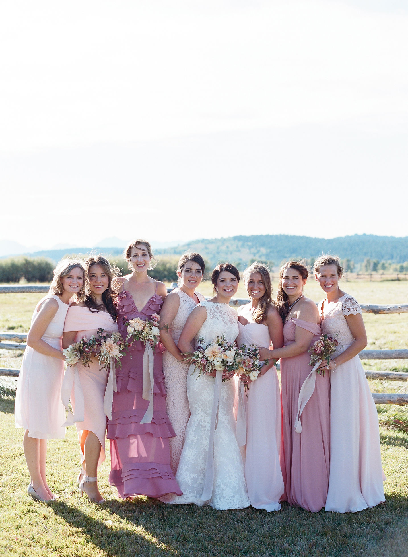 bridesmaids wearing shades of blush dresses in various styles