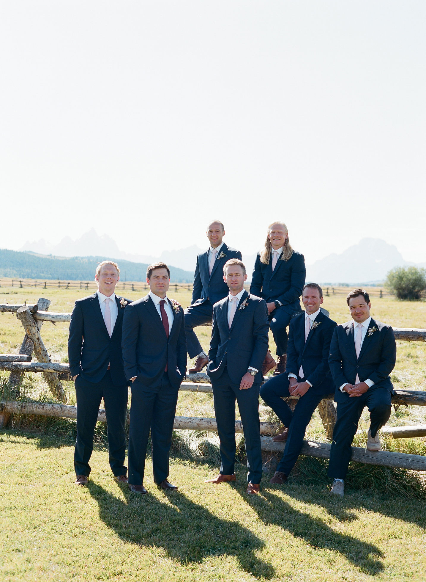 groomsmen wearing navy suits outside