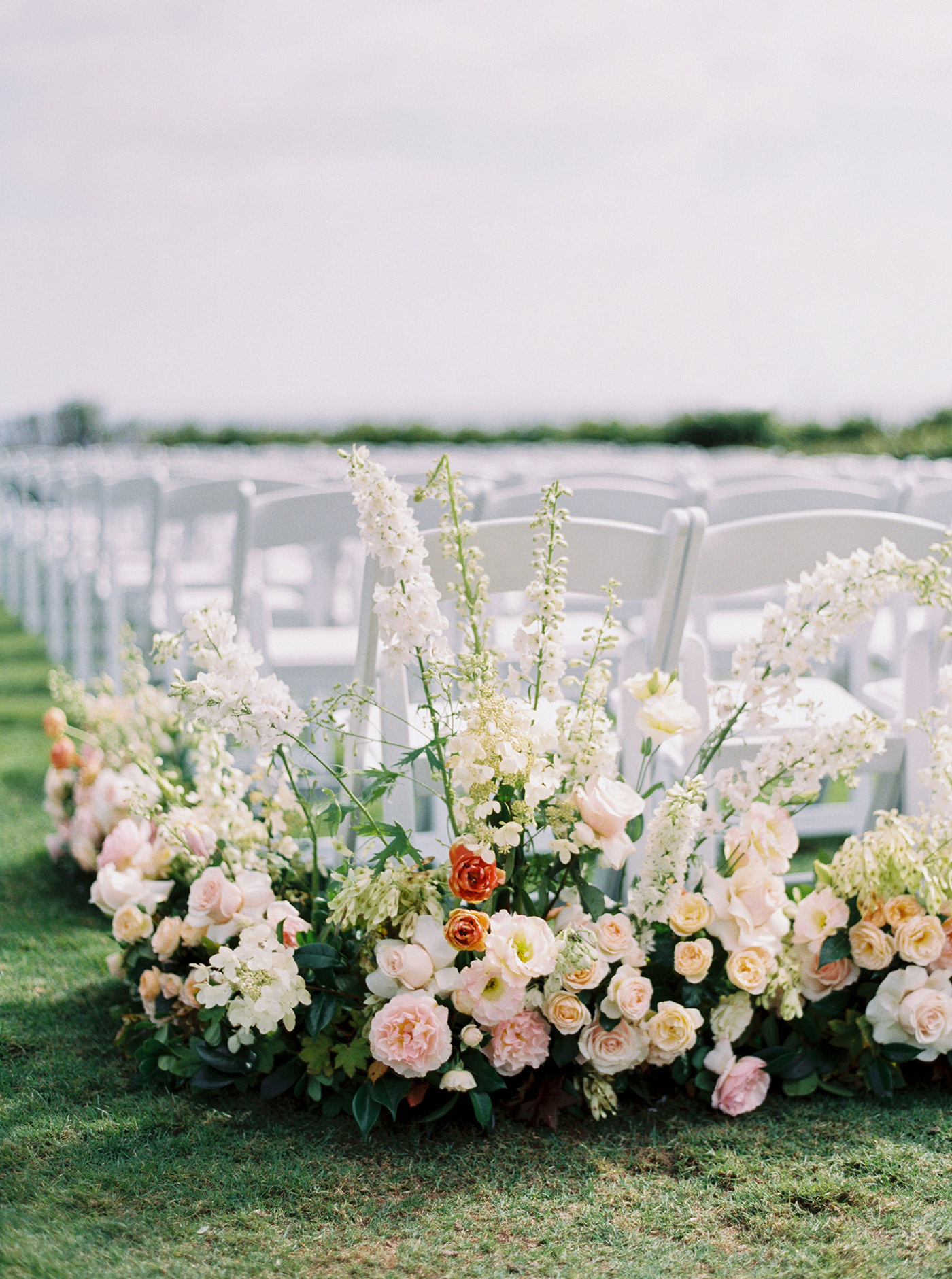 mykaela and brendon wedding ceremony chairs decorated with roses and greenery