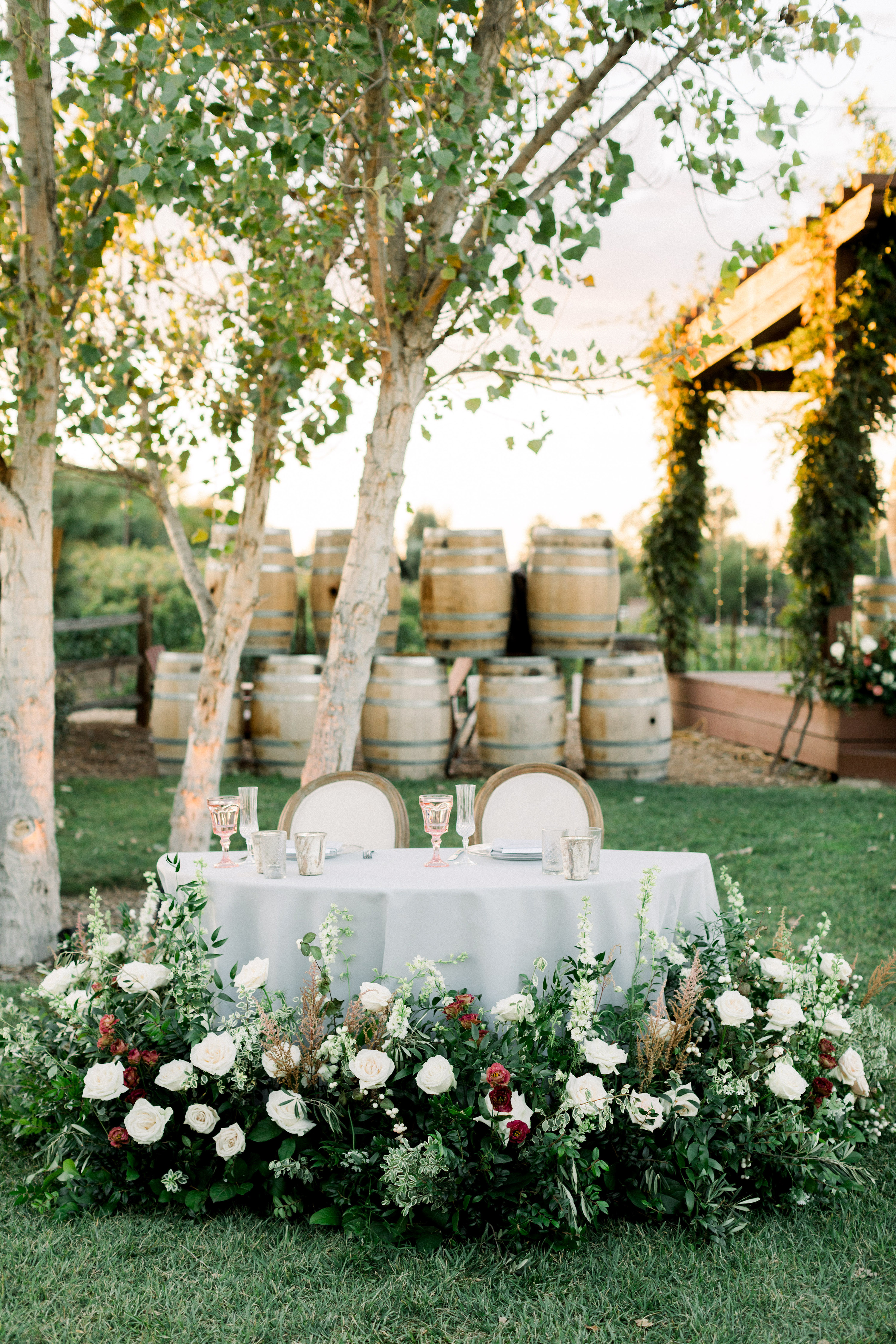 sweetheart table outdoor with barrels backdrop and roses around foot of table