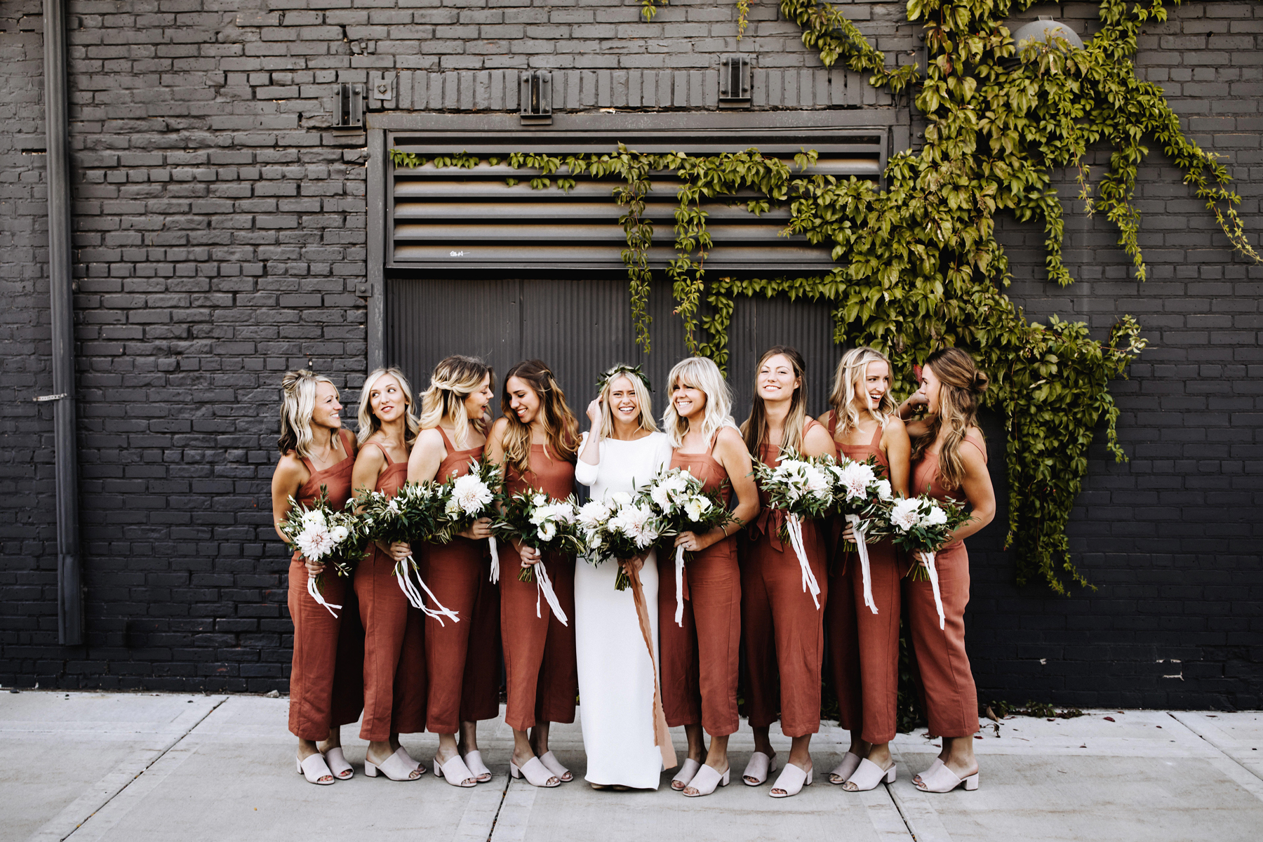 women standing in front of black brick wearing bridesmaids jumpsuits