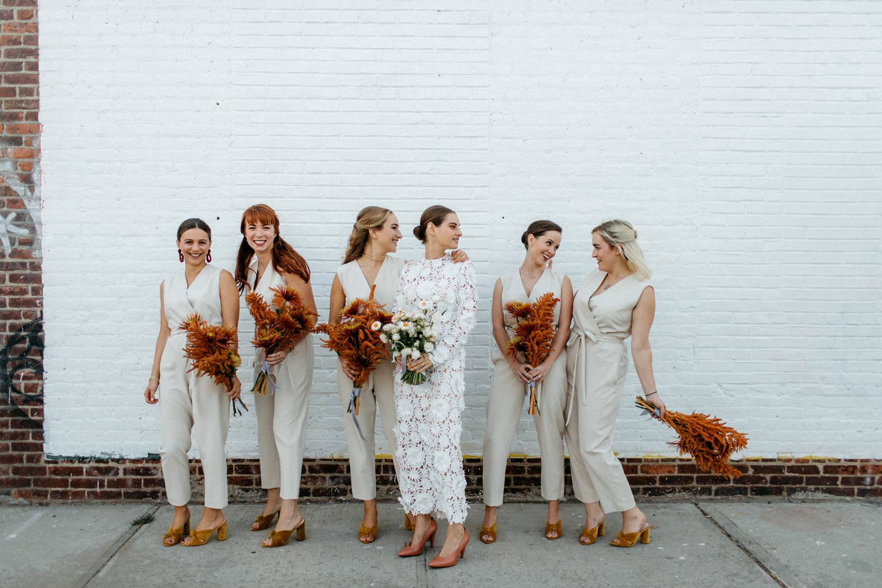 women in front of white brick wearing bridesmaids jumpsuits