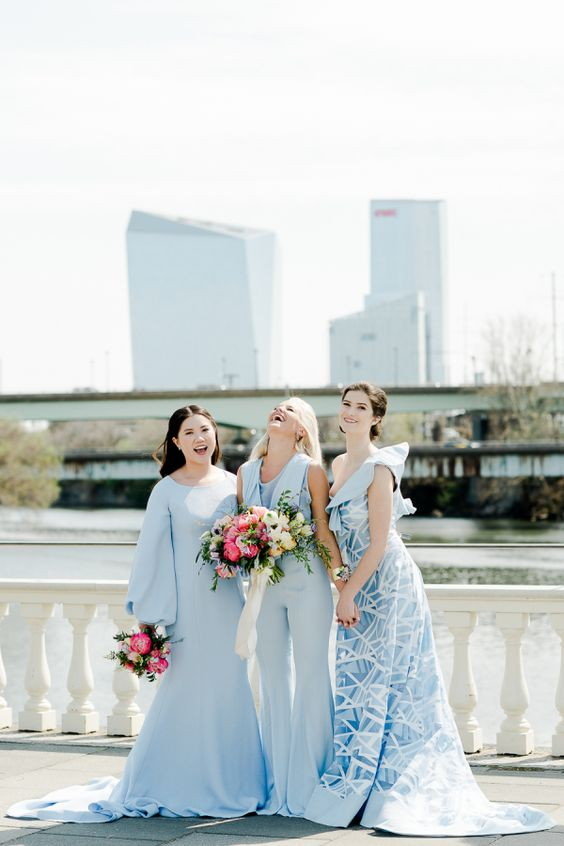 women standing on bridge wearing pale blue bridesmaid dresses and jumpsuit