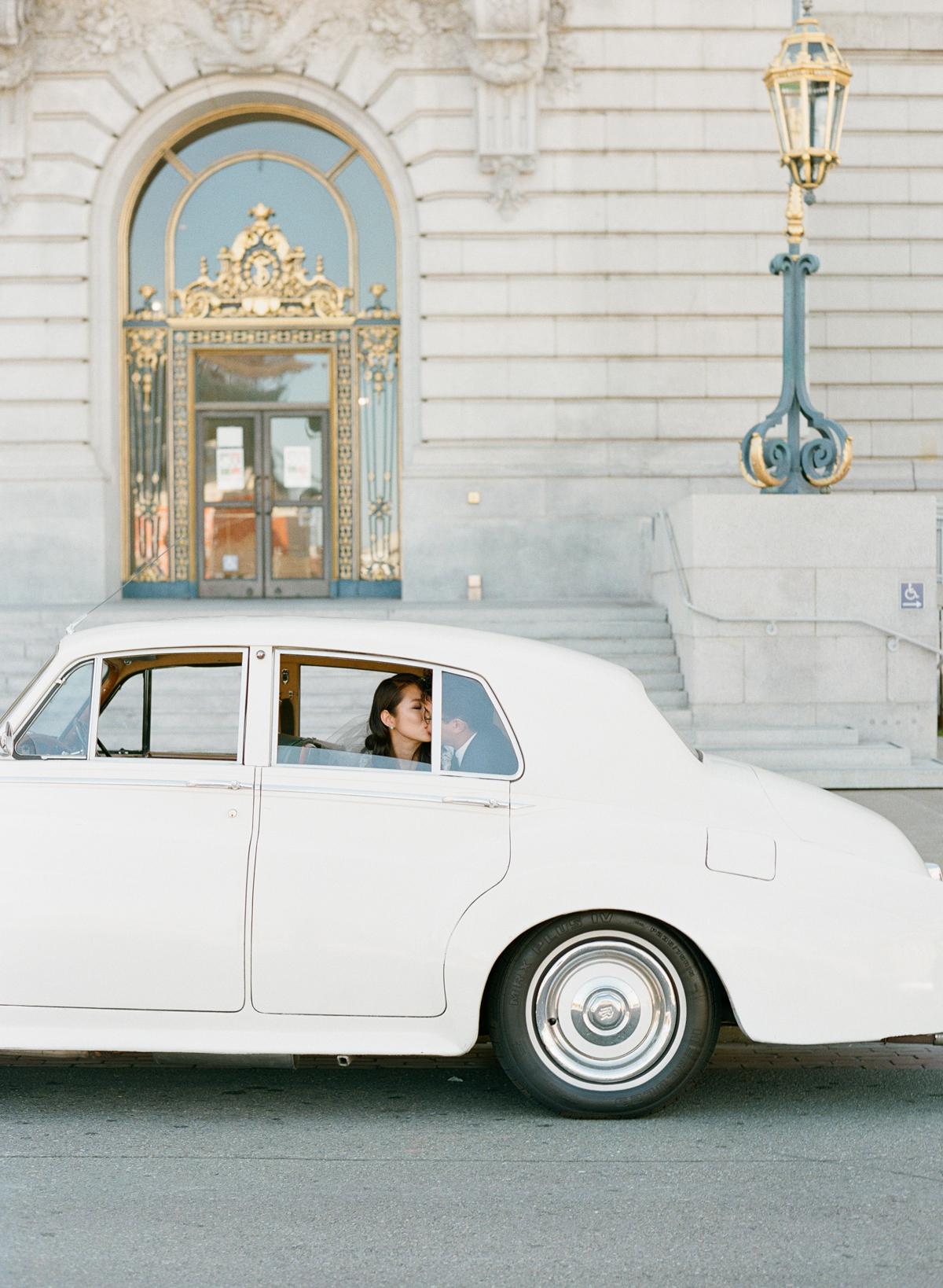 bride and groom sitting in back of white vintage getaway car