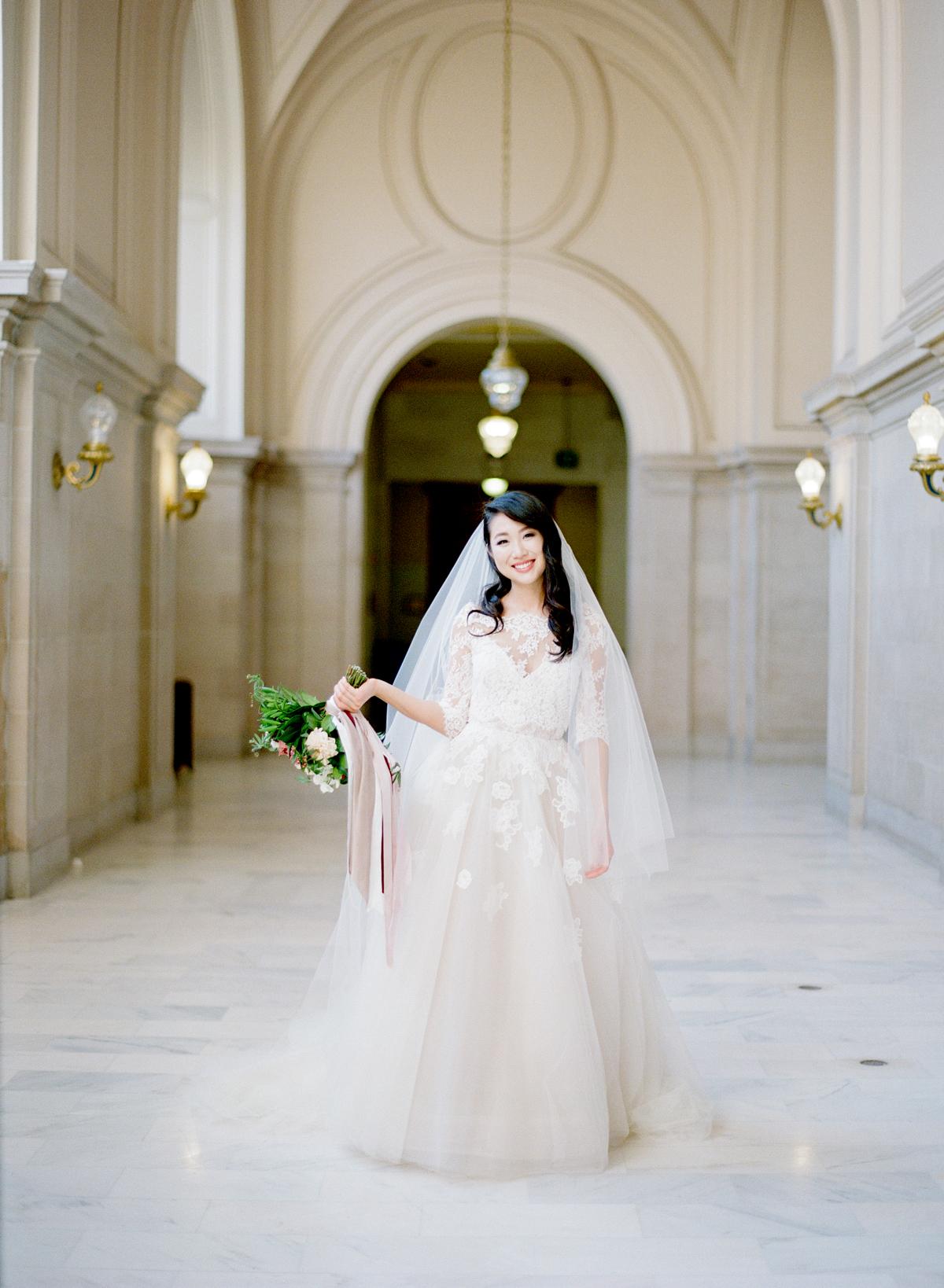 bride wearing Monique Lhuillier wedding dress to city hall venue