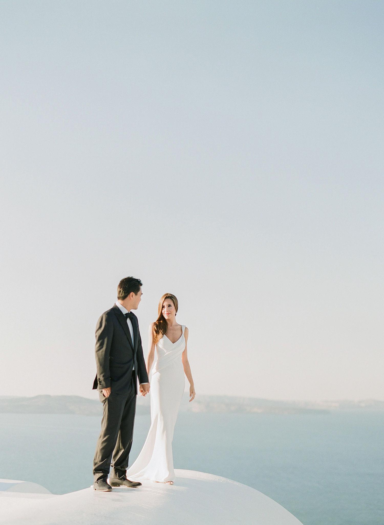 bride and groom standing on Greek coast