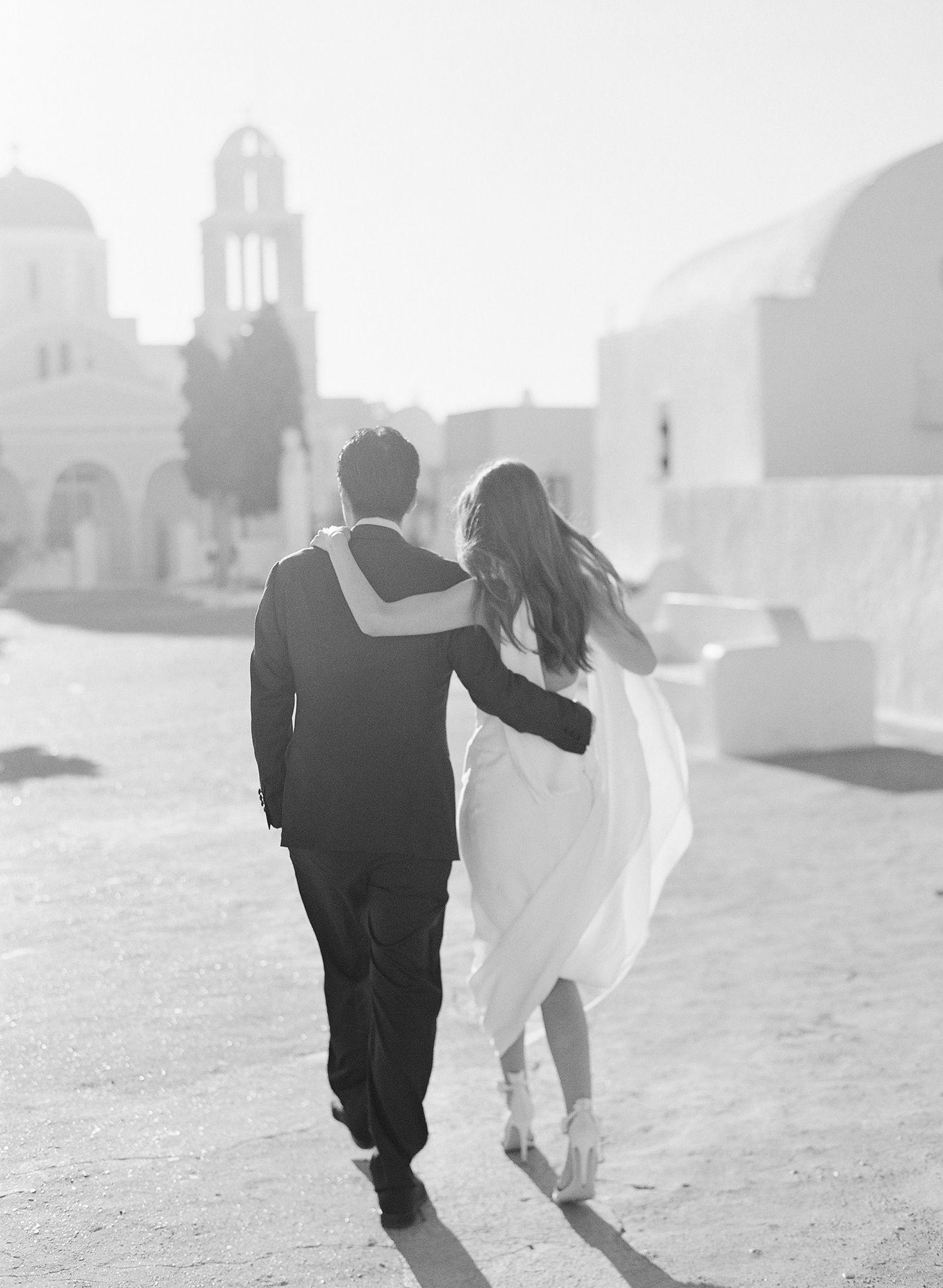 bride and groom running through greek city