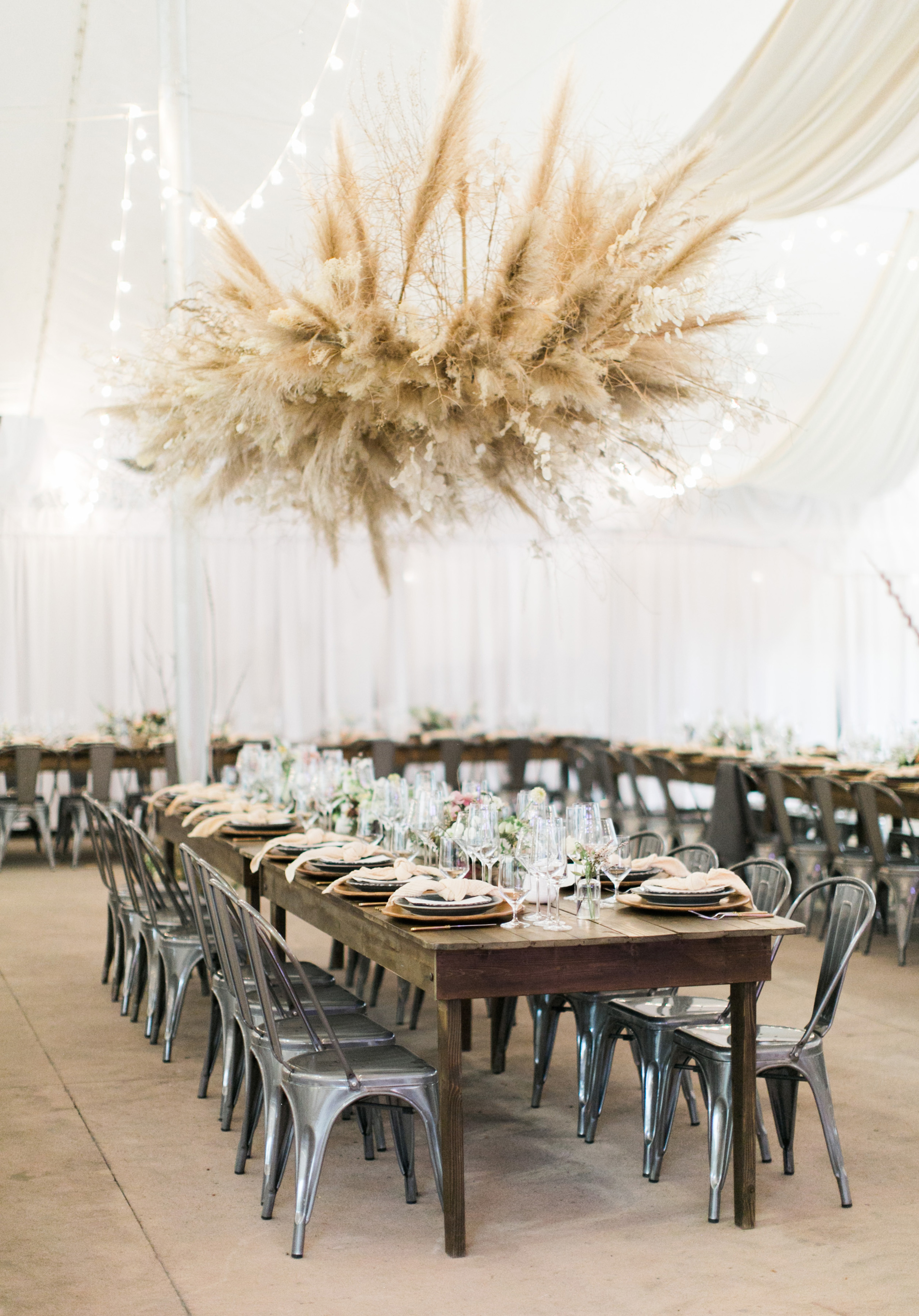 white tent wedding reception filled with hanging floral decor, rustic tables, and string lights
