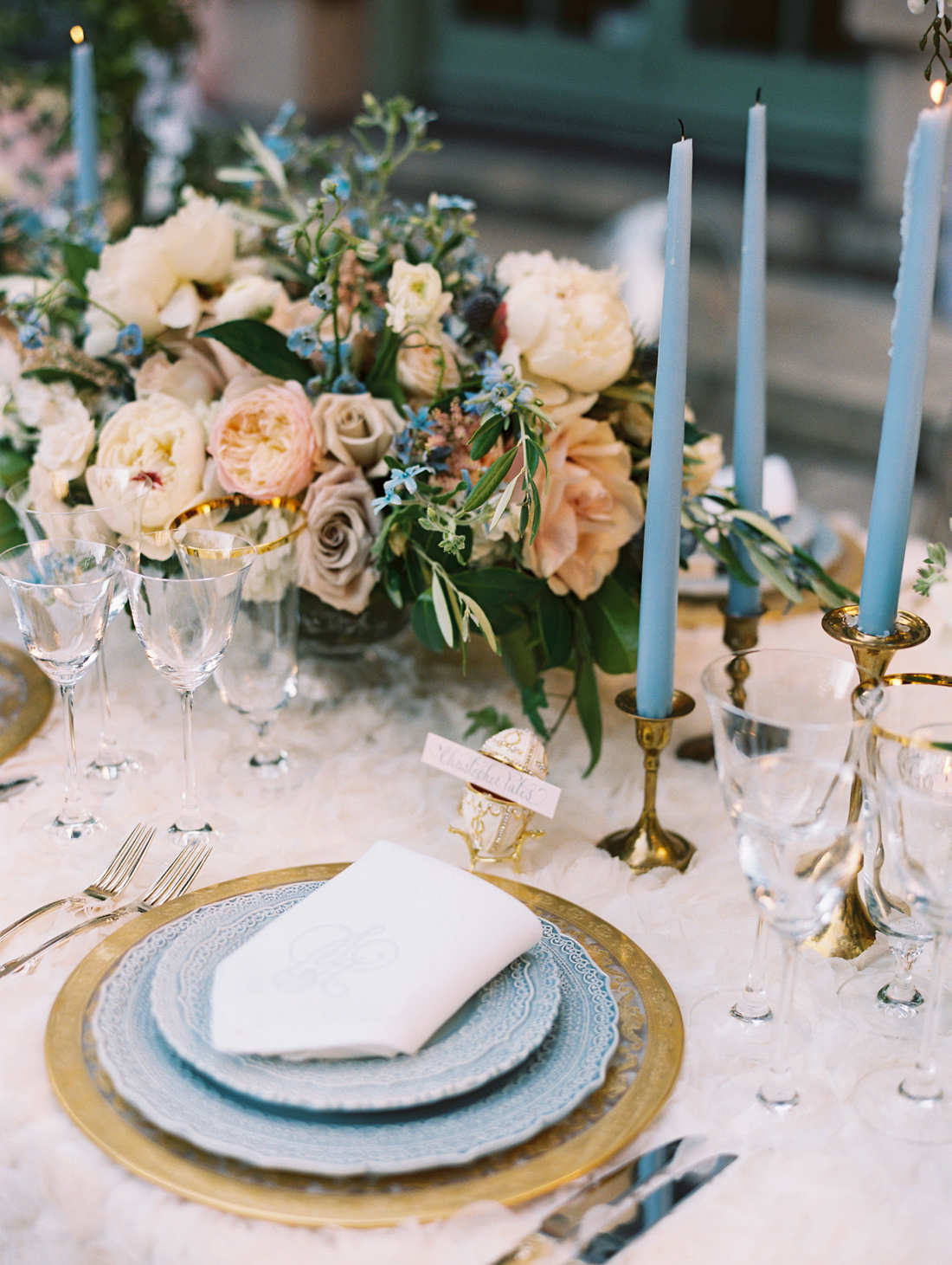 baby blue and gold themed place settings with floral centerpieces