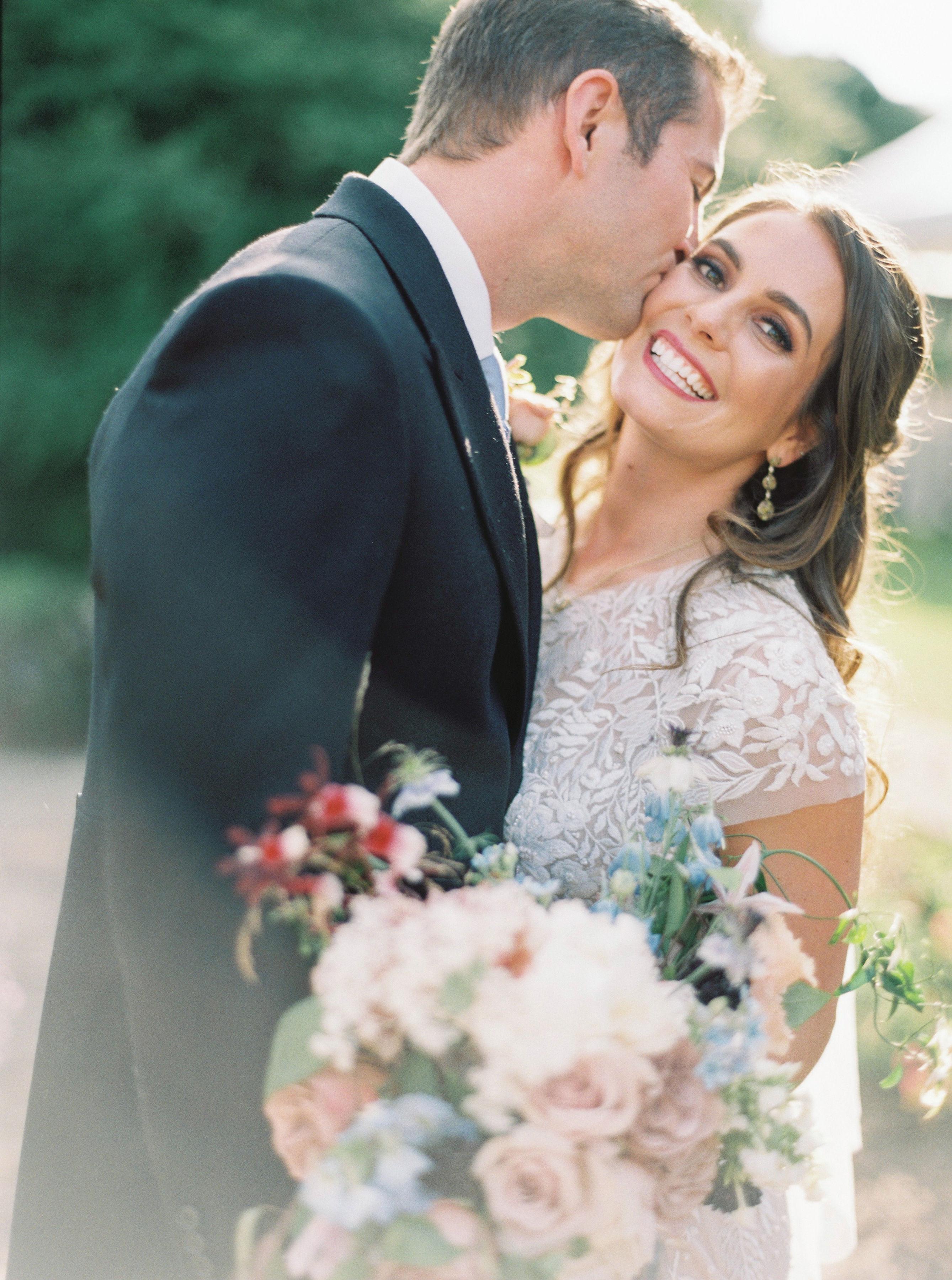 groom kissing bride on cheek outside smiling