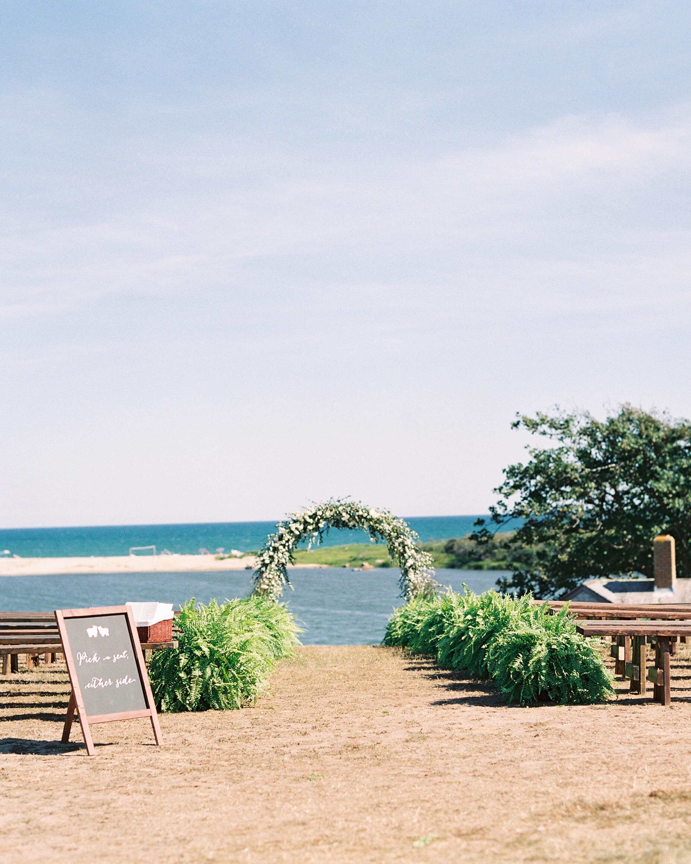 floral arch and wooden benches on beach front wedding ceremony venue