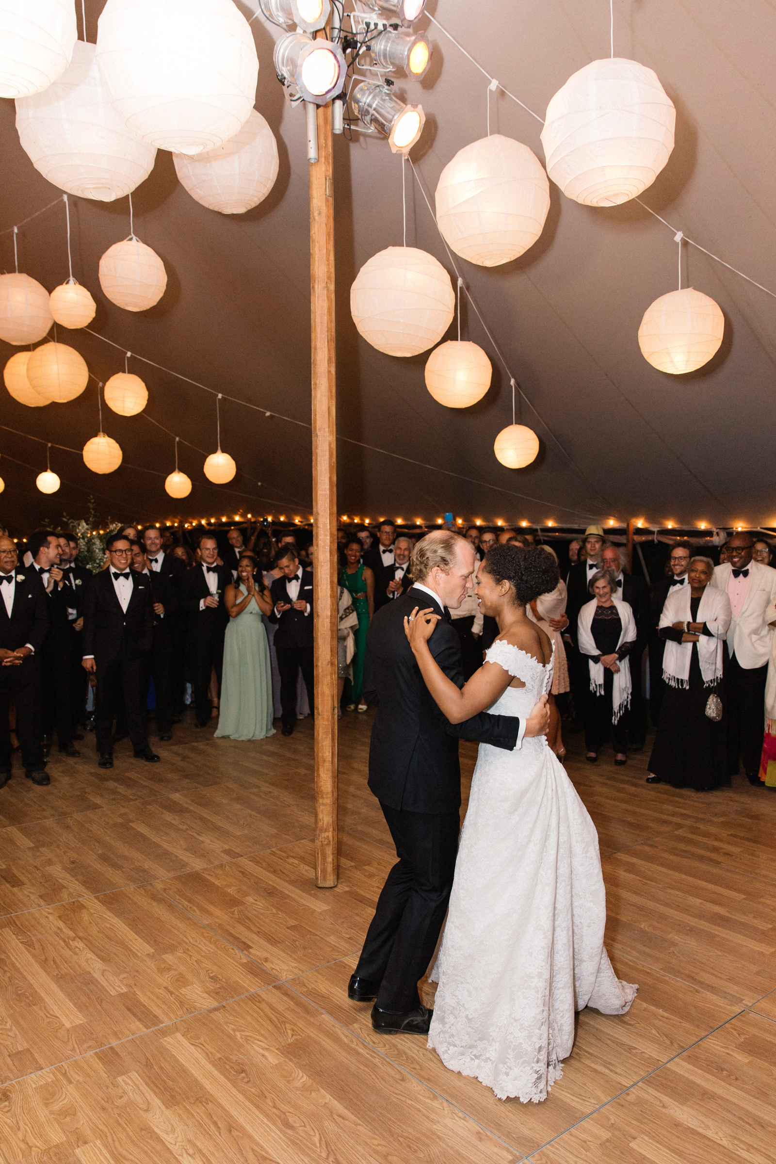 bride and groom share first dance surrounded by guests under hanging lanterns