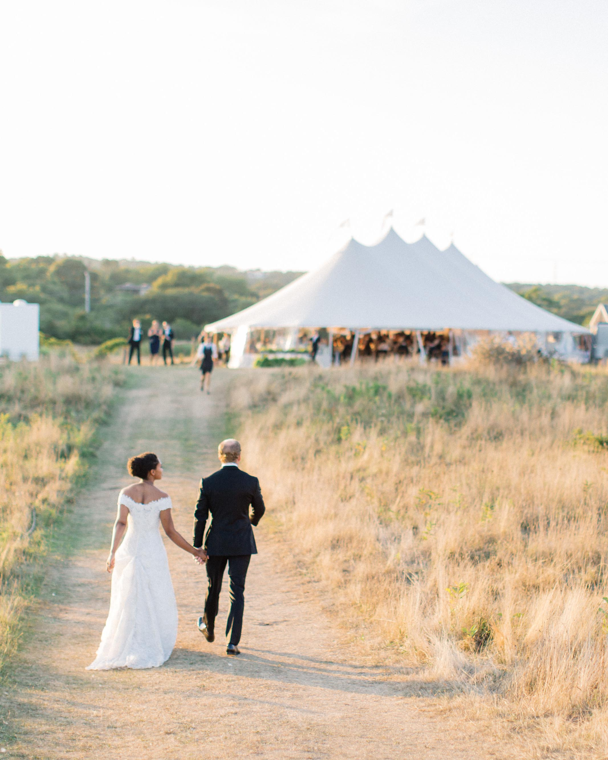 bride and groom walking toward large white reception wedding tent