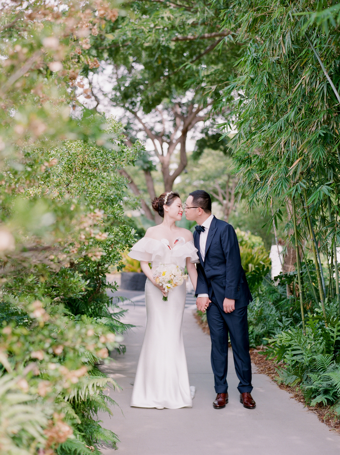bride and groom walking on outdoor pathway