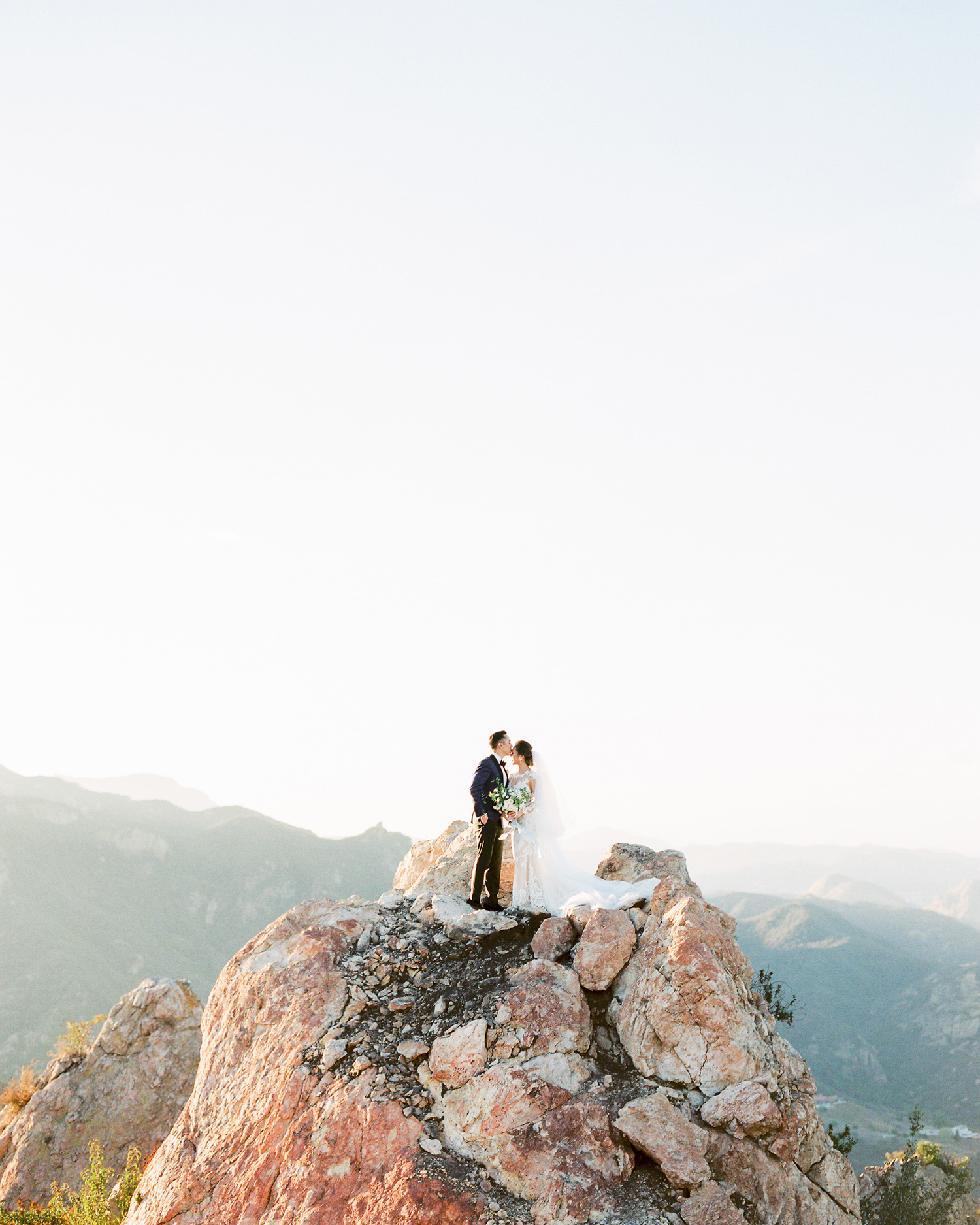 sunset wedding photos groom kissing bride on cliff with mountainous background