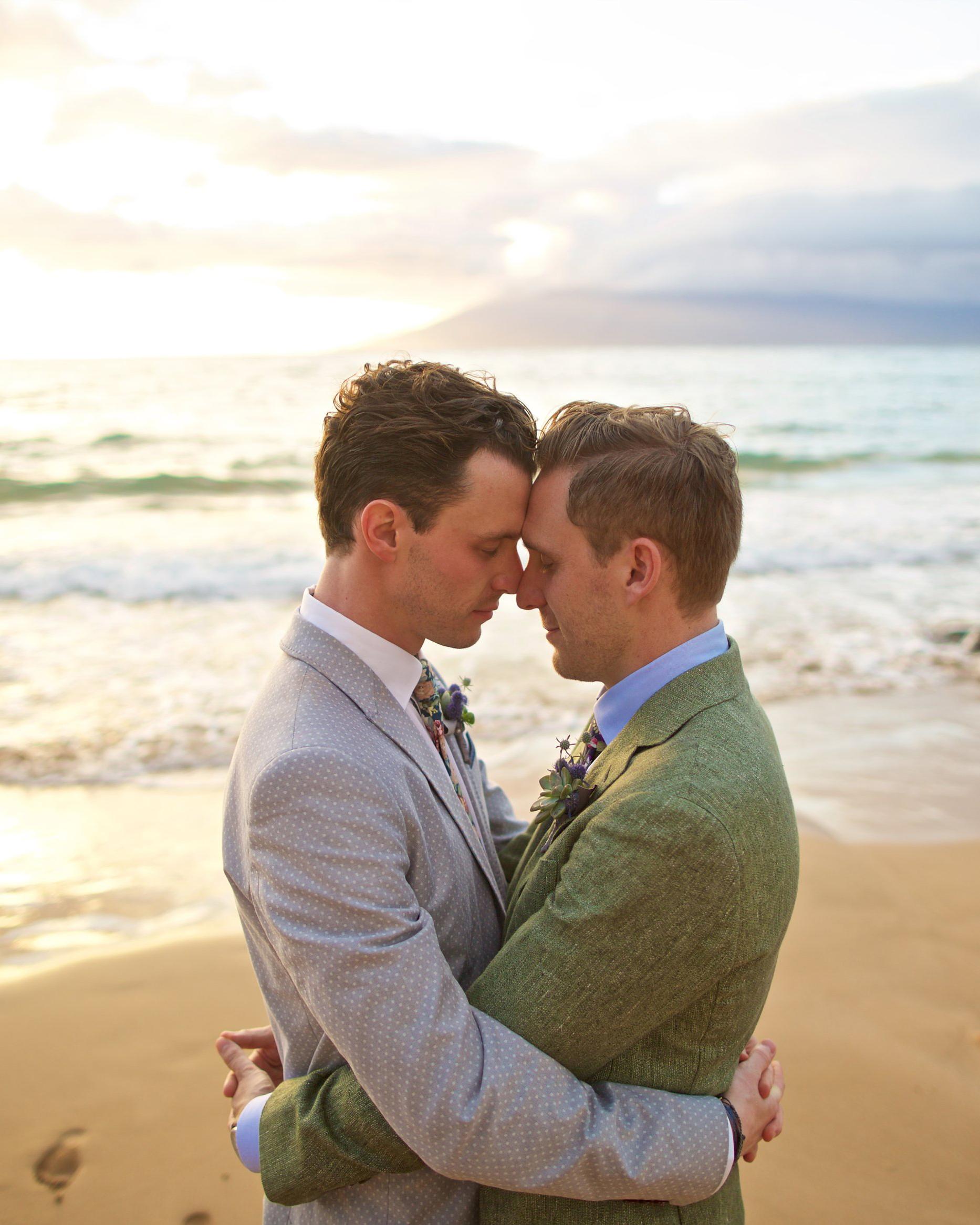 sunset wedding photos grooms embracing on beach