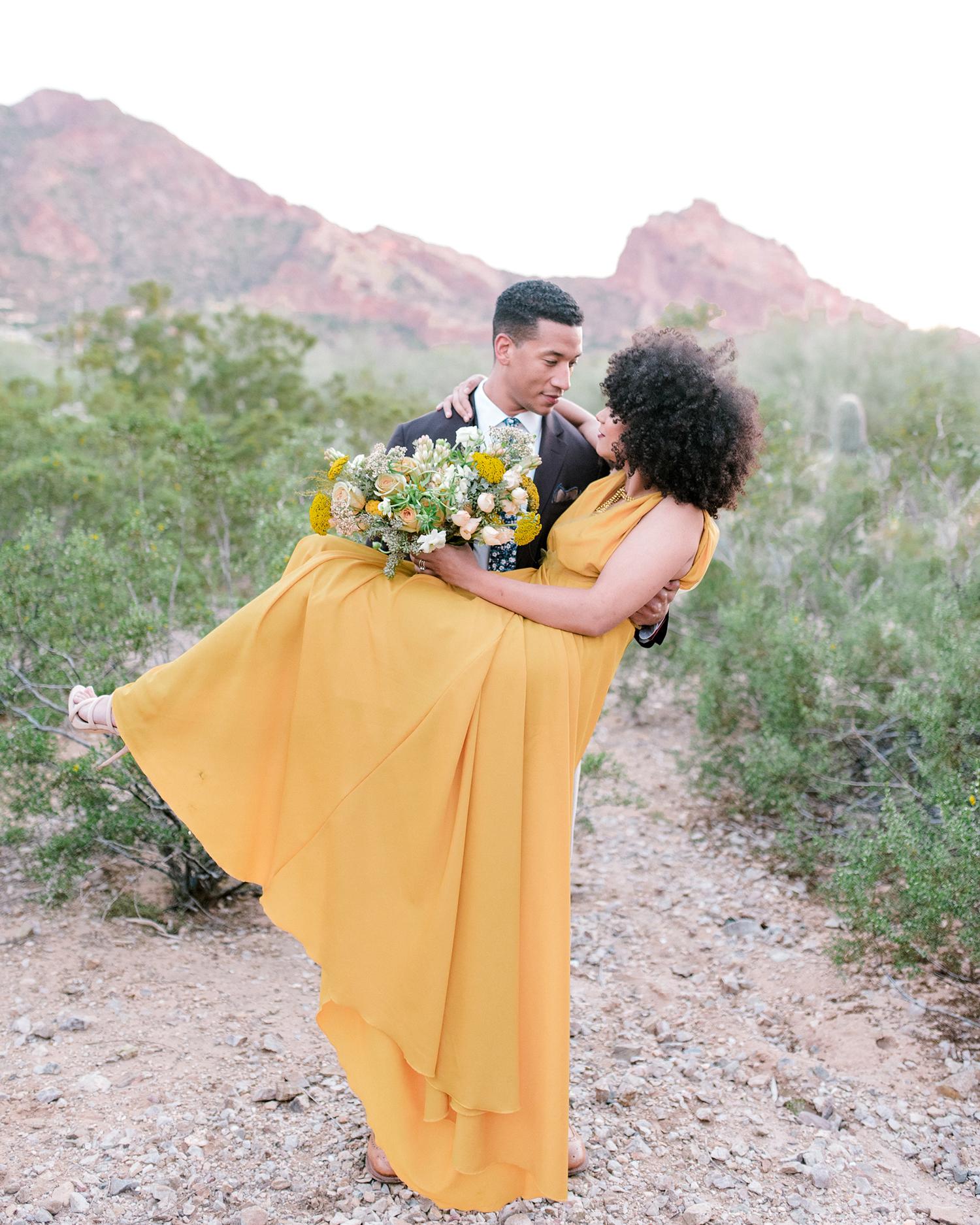 sunset wedding photos groom carrying bride in desert