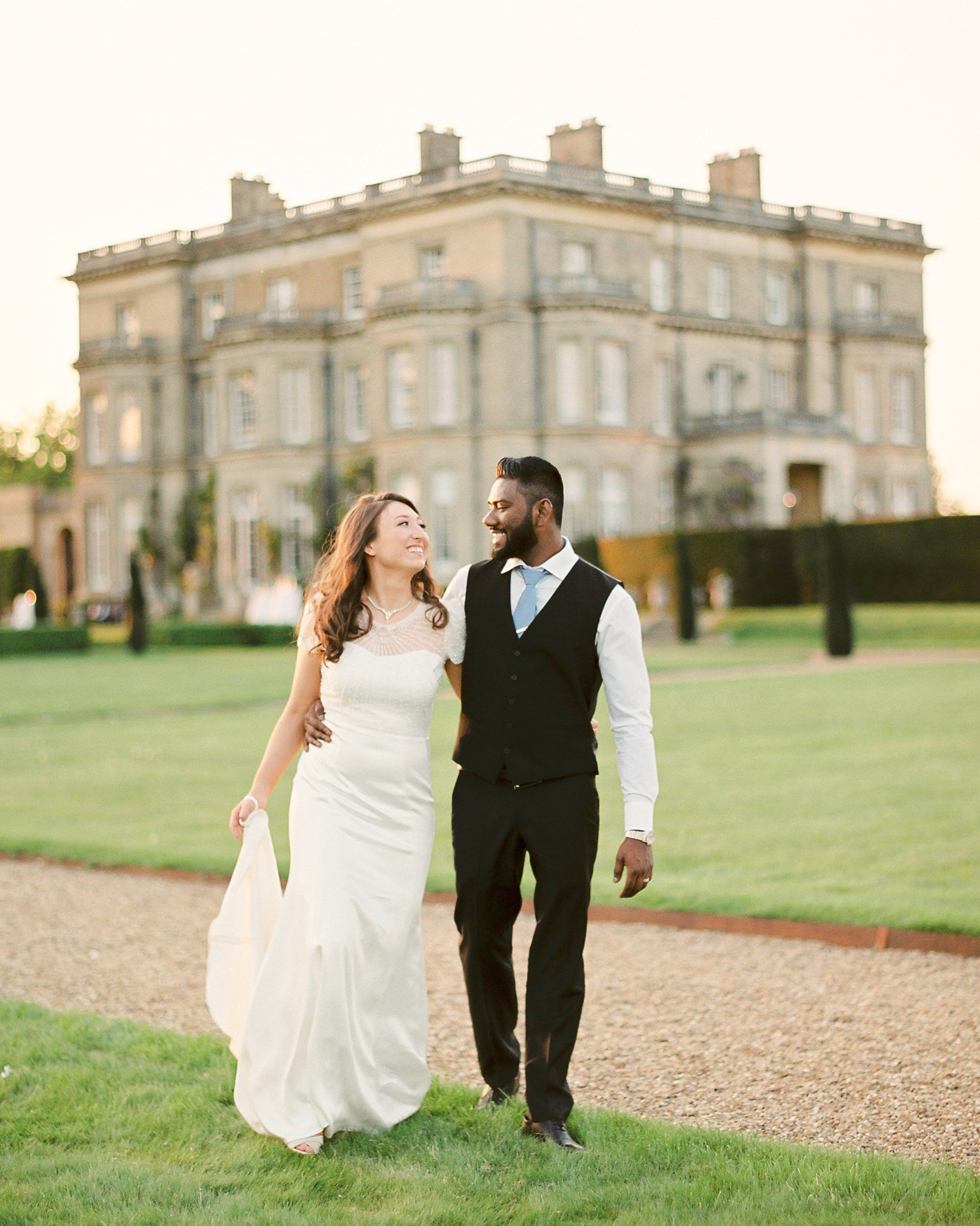 sunset wedding photos bride and groom walking in front of estate venue