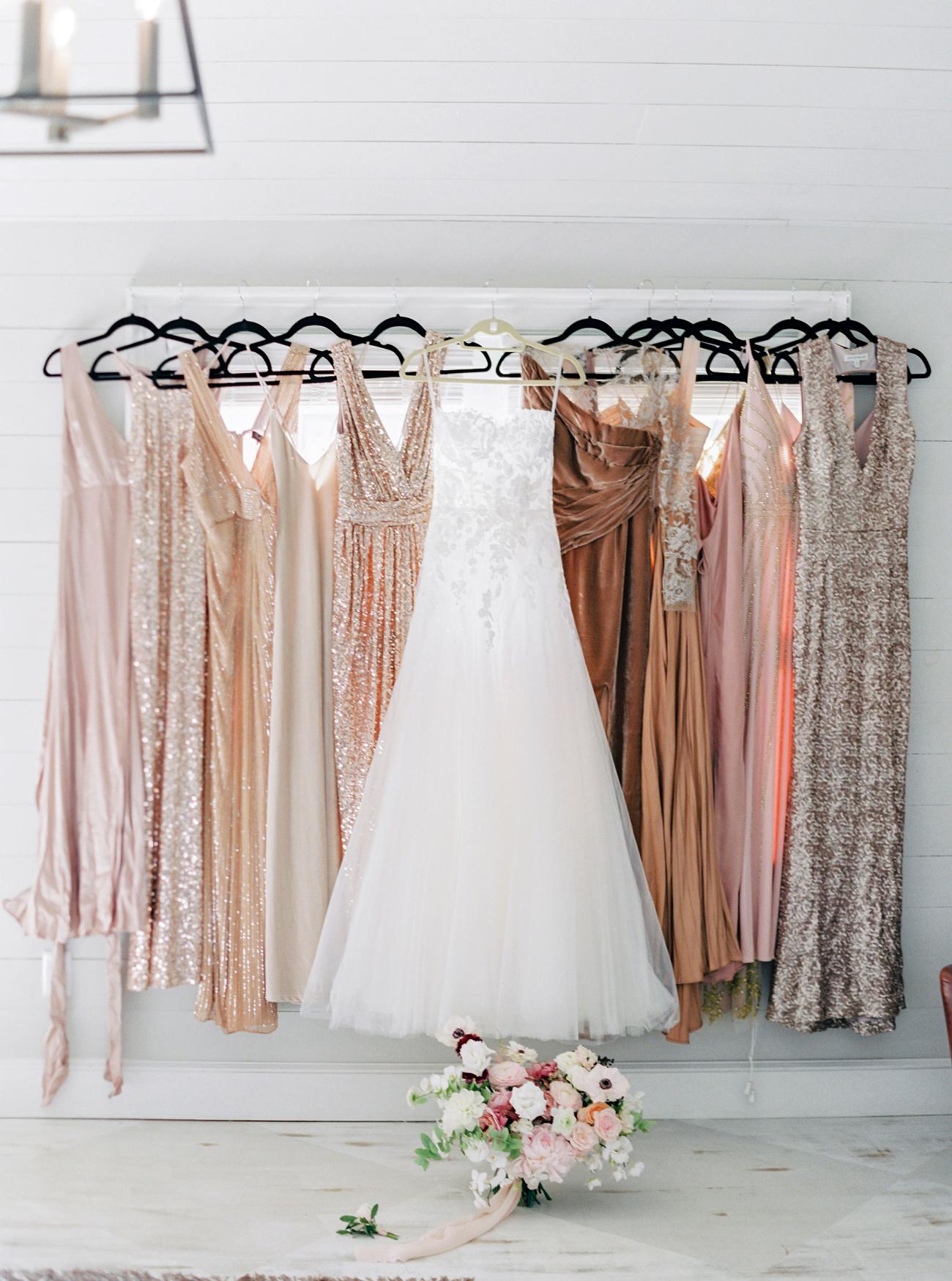 bride's hanging custom mira zwillinger wedding dress with blush and peach tone glittery bridesmaids dresses