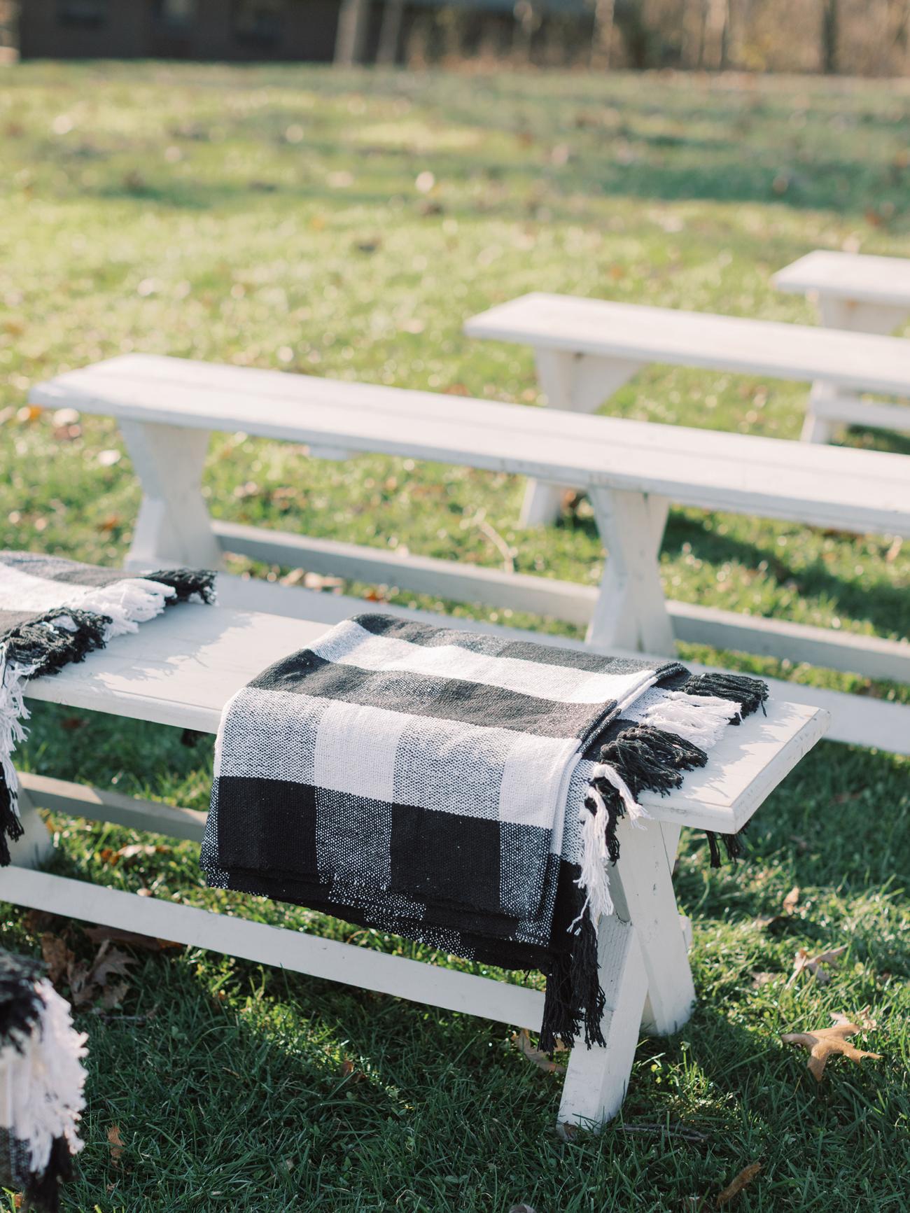 black and white buffalo check blanket wraps on white wedding ceremony benches