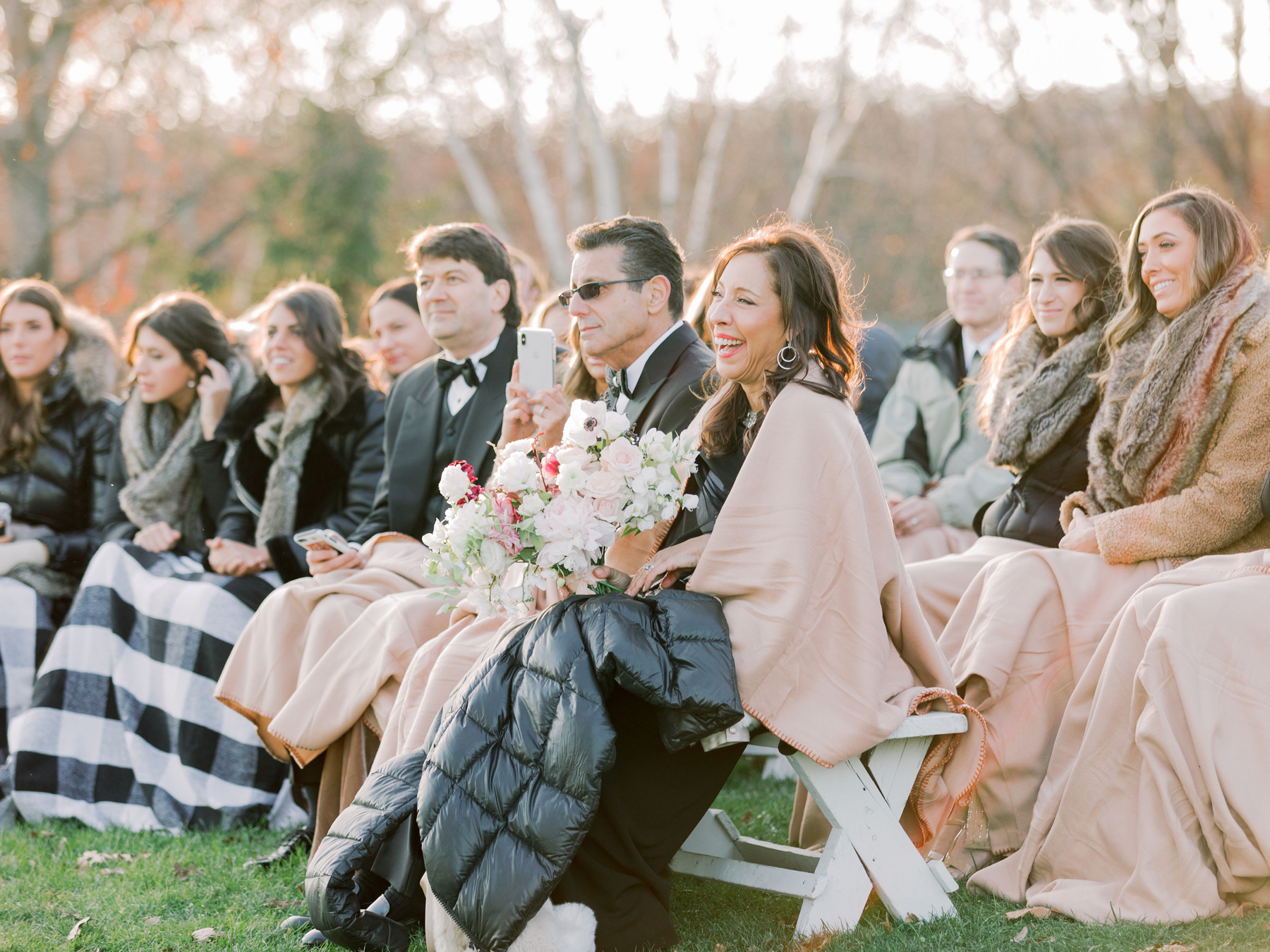 wedding guests with shawls and blankets during outdoor wedding ceremony