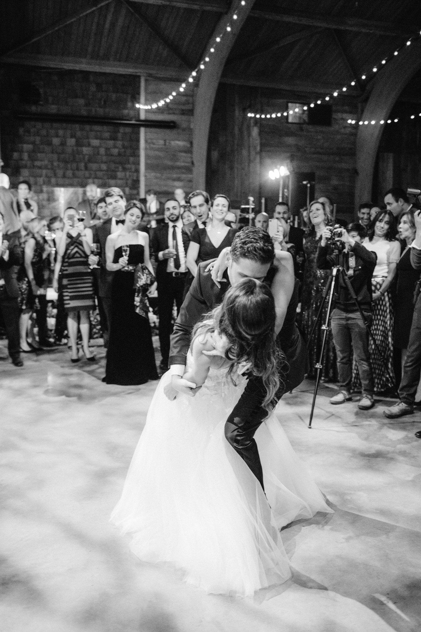 groom dips bride during first dance surrounded by wedding guests