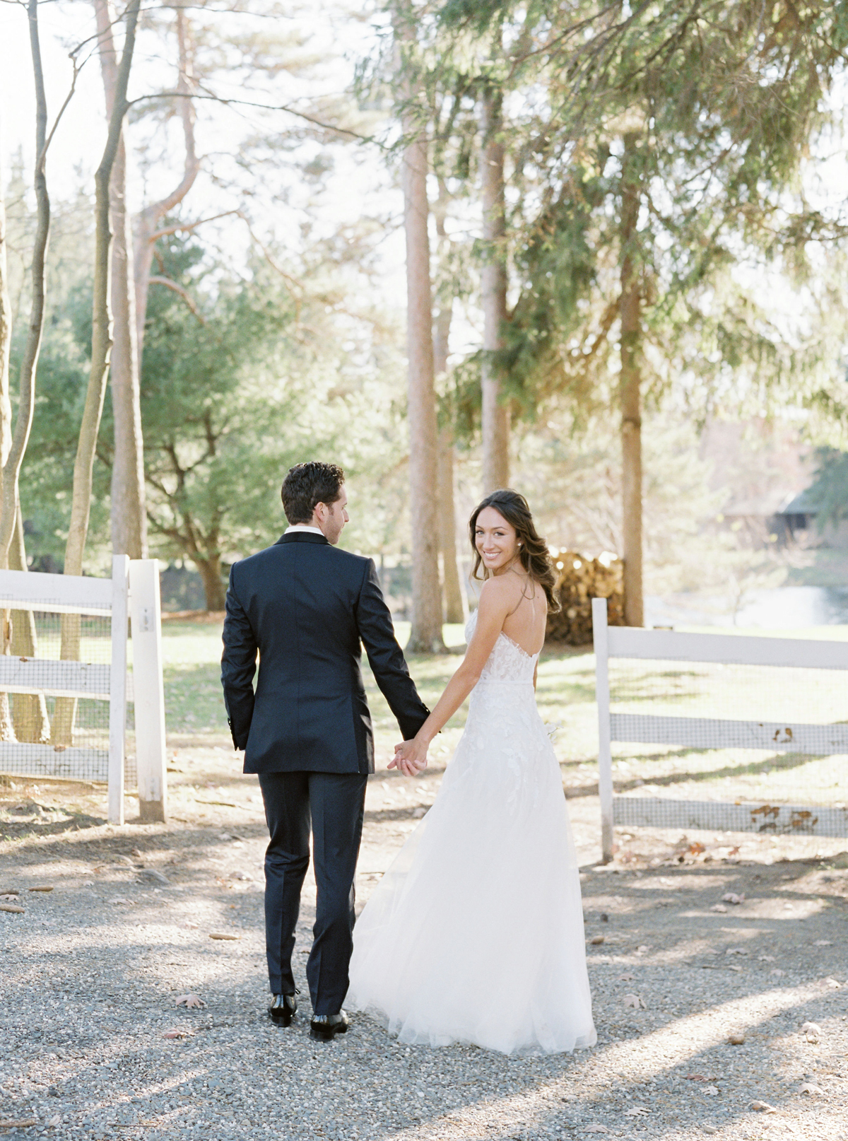 bride and groom holding hands outside near white fence