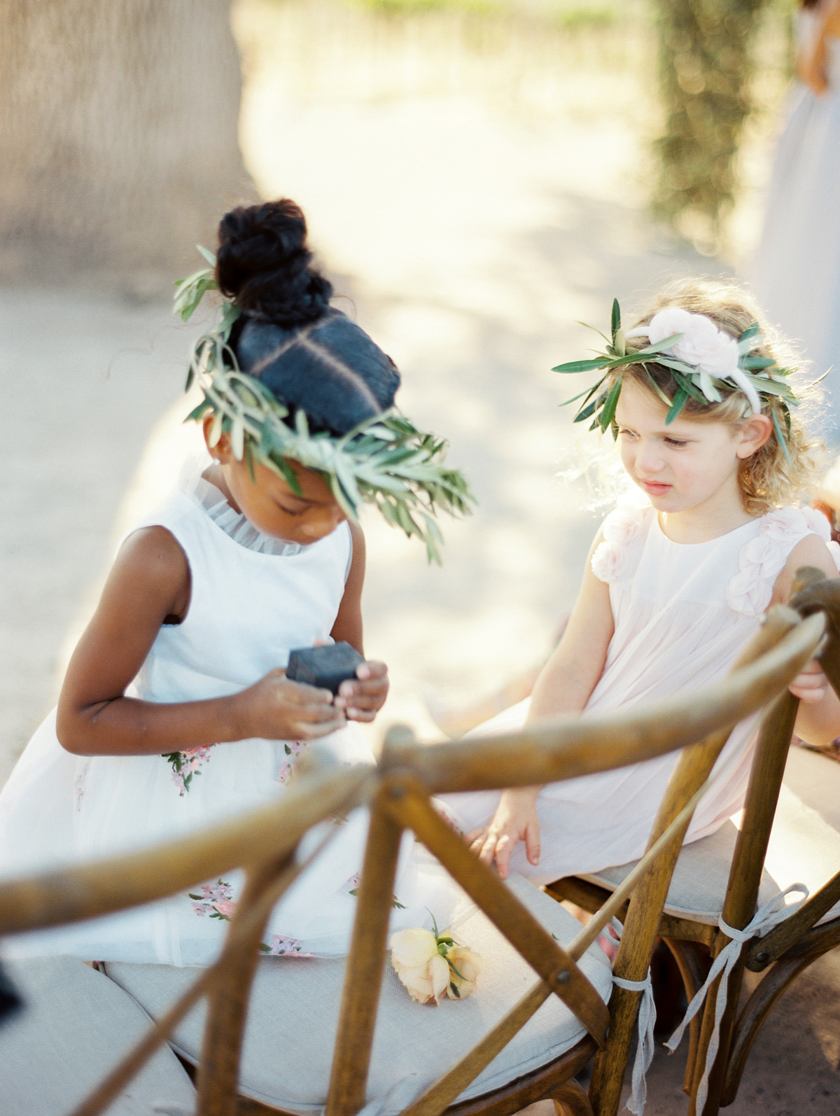 flower girls wearing white dresses and olive leaf crowns