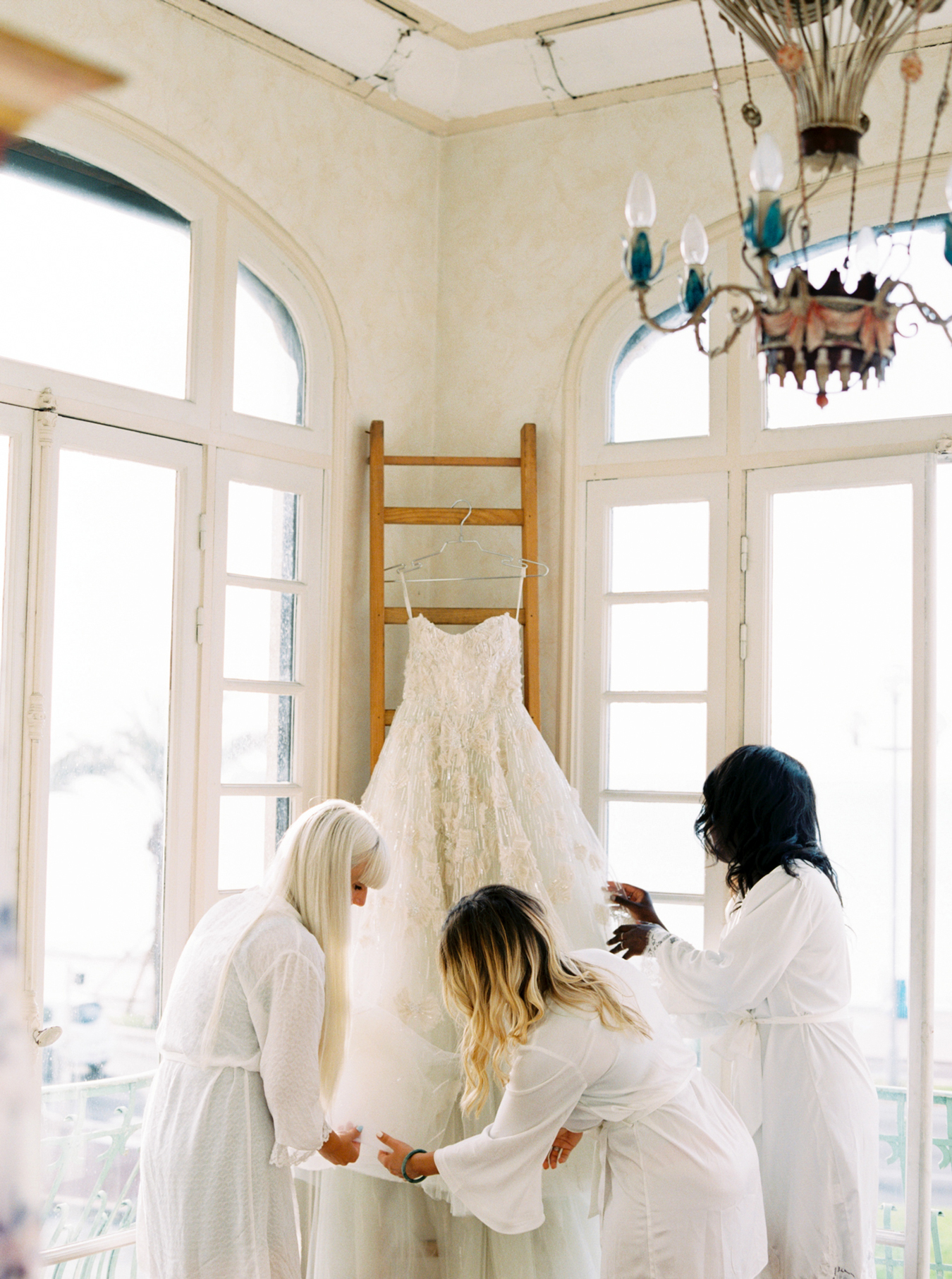 bridesmaids gathered around hanging wedding dress ball gown