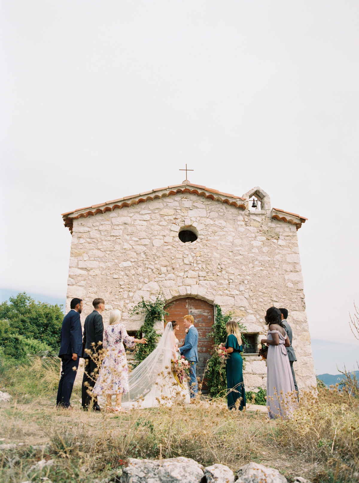 bride and groom stand with 6 friend outside stone church
