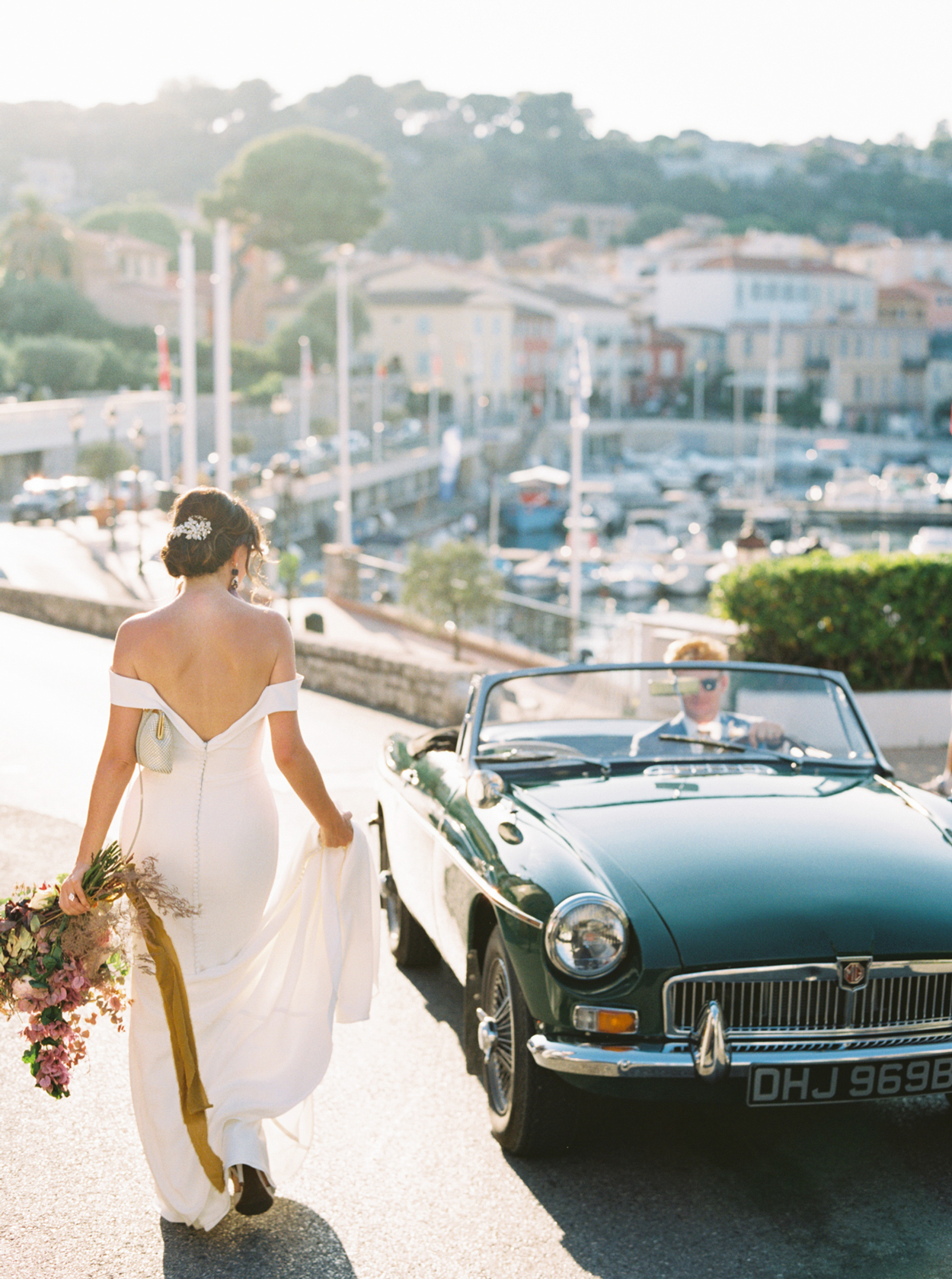 bride wearing Phoebe by Kelly Faetanini next to vintage car