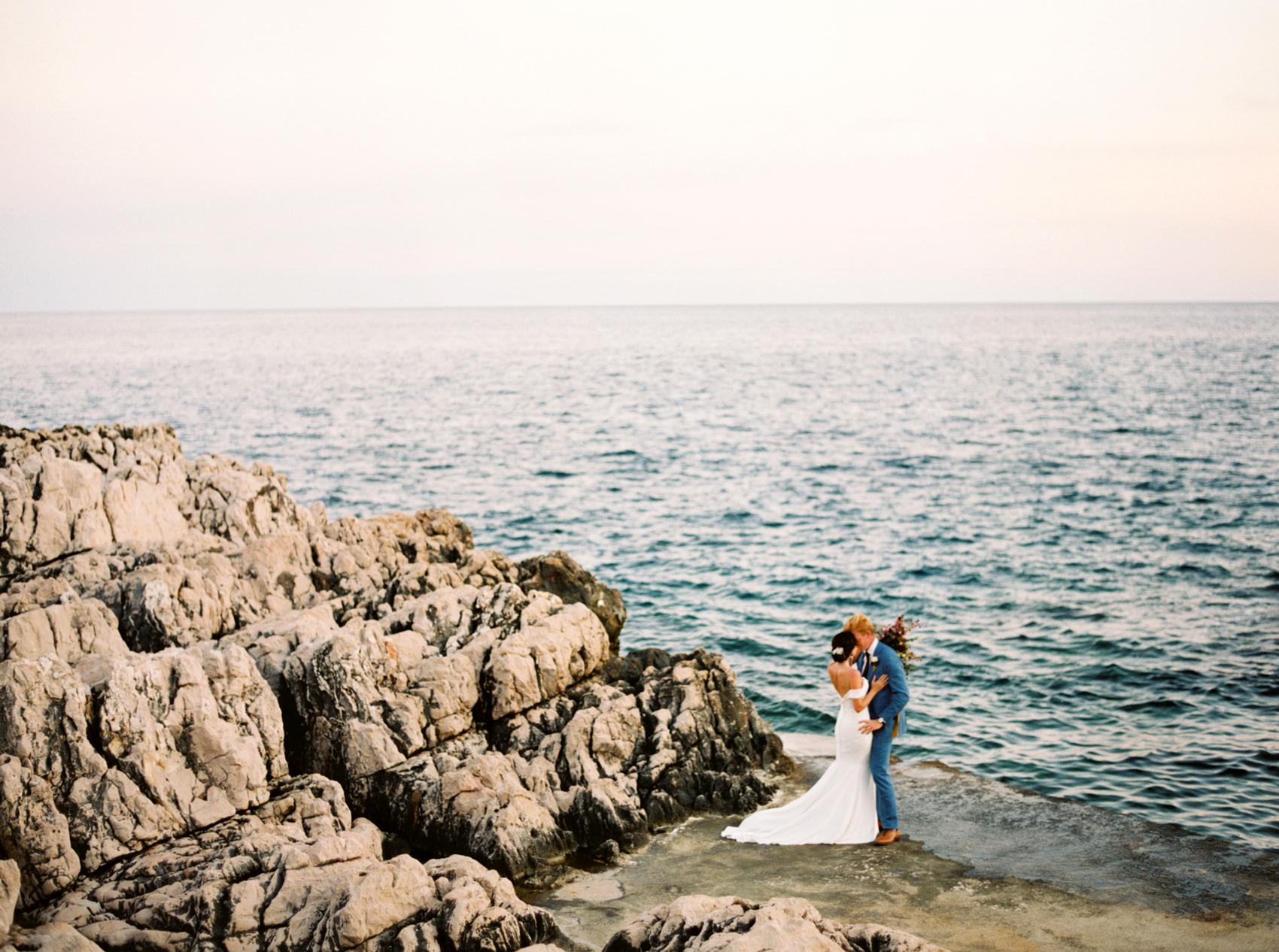 bride and groom oceanside kissing