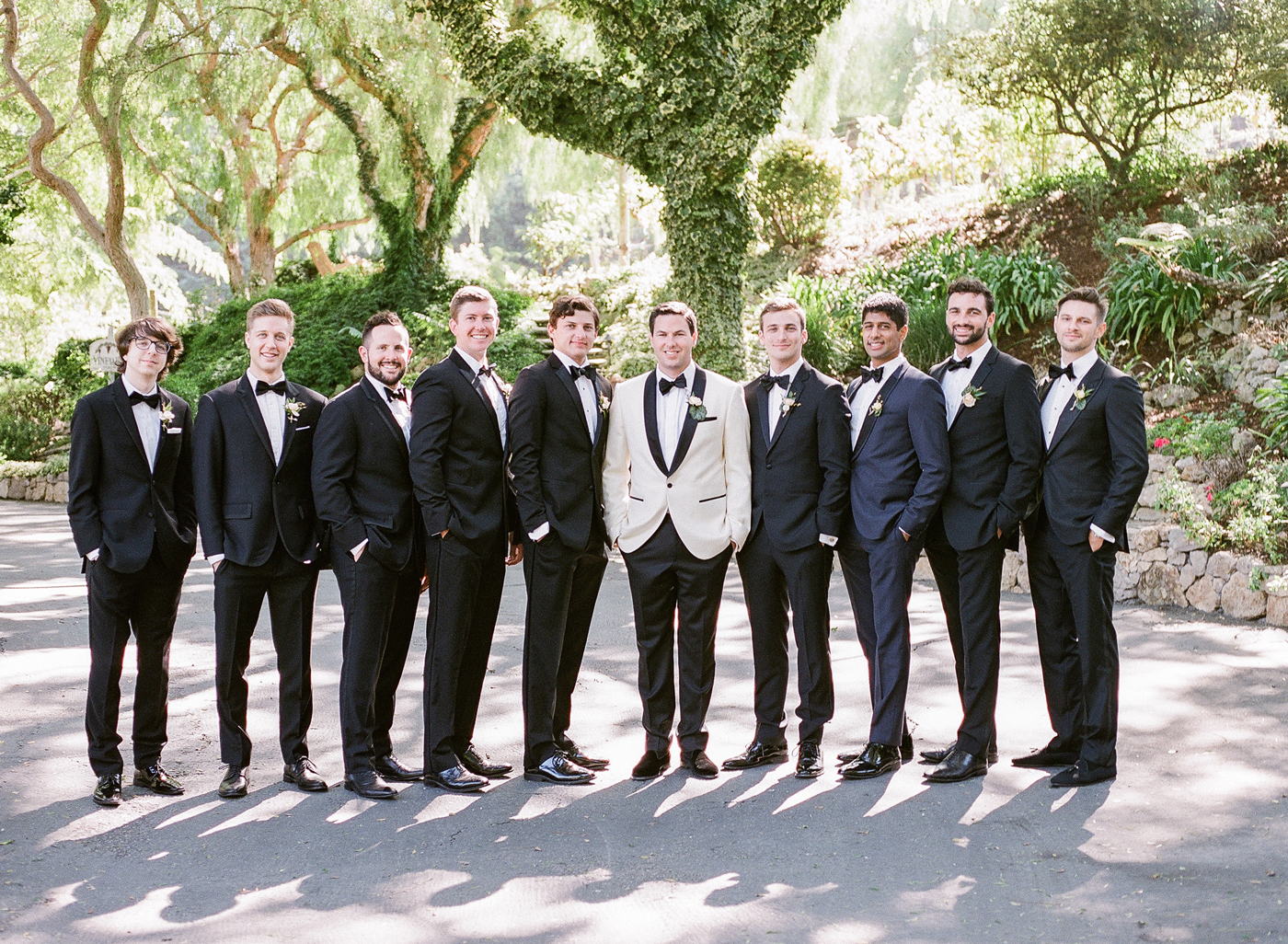 groom with groomsmen all wearing black suits and bowties