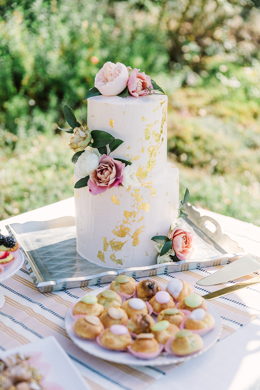 two tier white frosted wedding cake with gold flakes