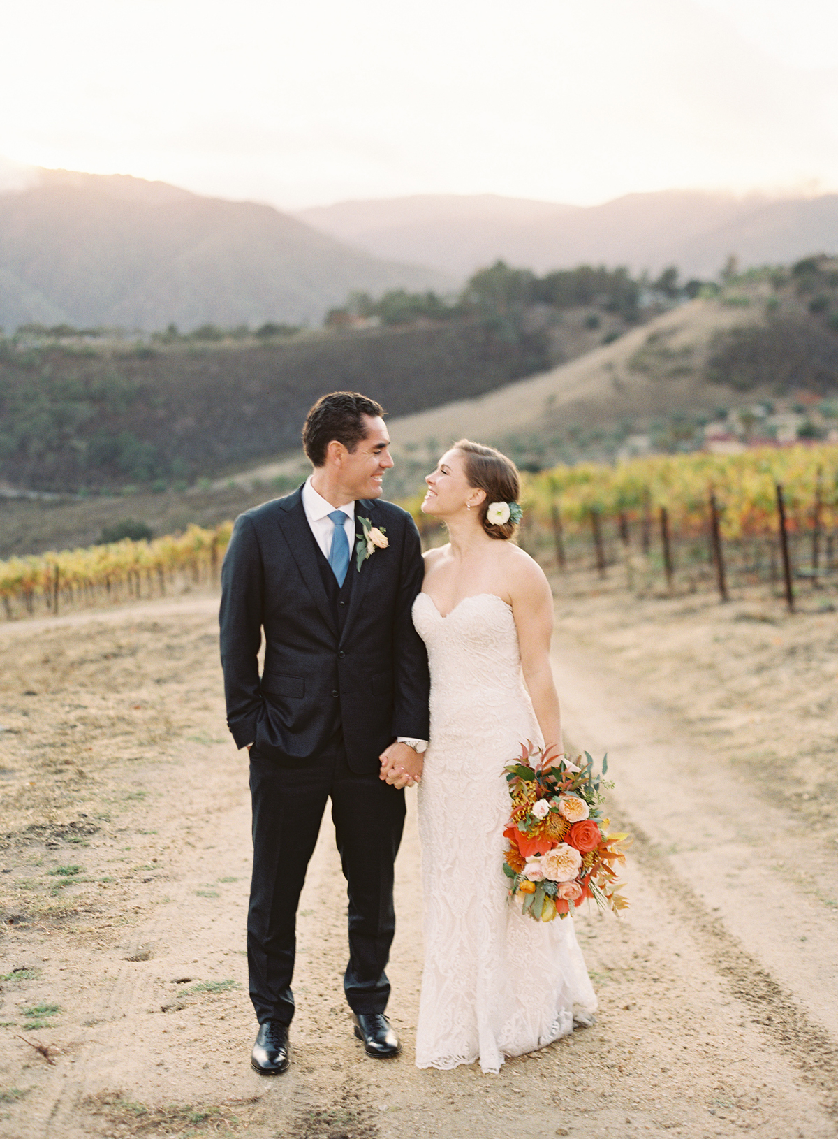 bride and groom holding hands smiling outside on ranch