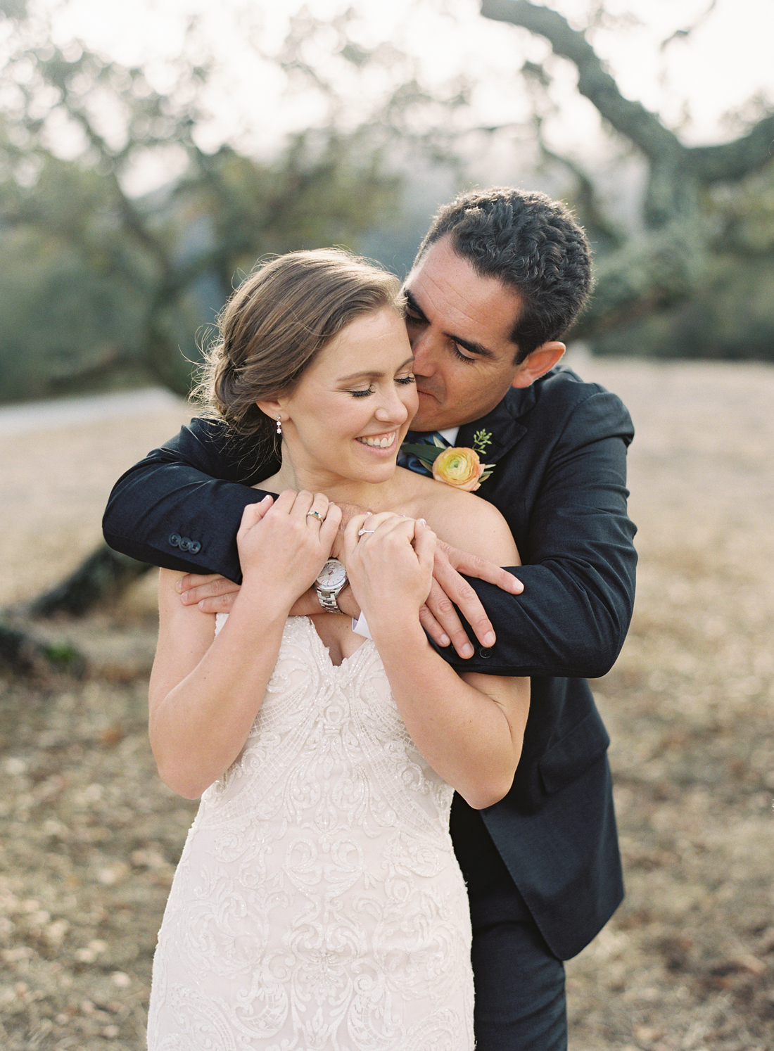 groom wrapping arms around bride from behind smiling